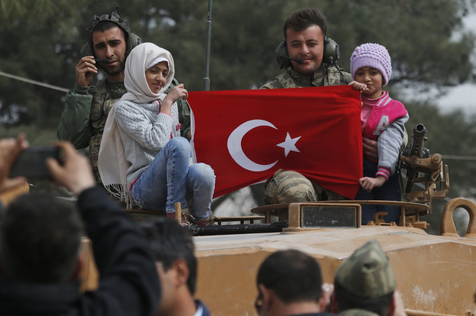 Turkish soldiers atop a tank pose for photos with Syrian children holding a Turkish flag, in the northwestern city of Afrin, Syria, March 24, 2018. (AP Photo)