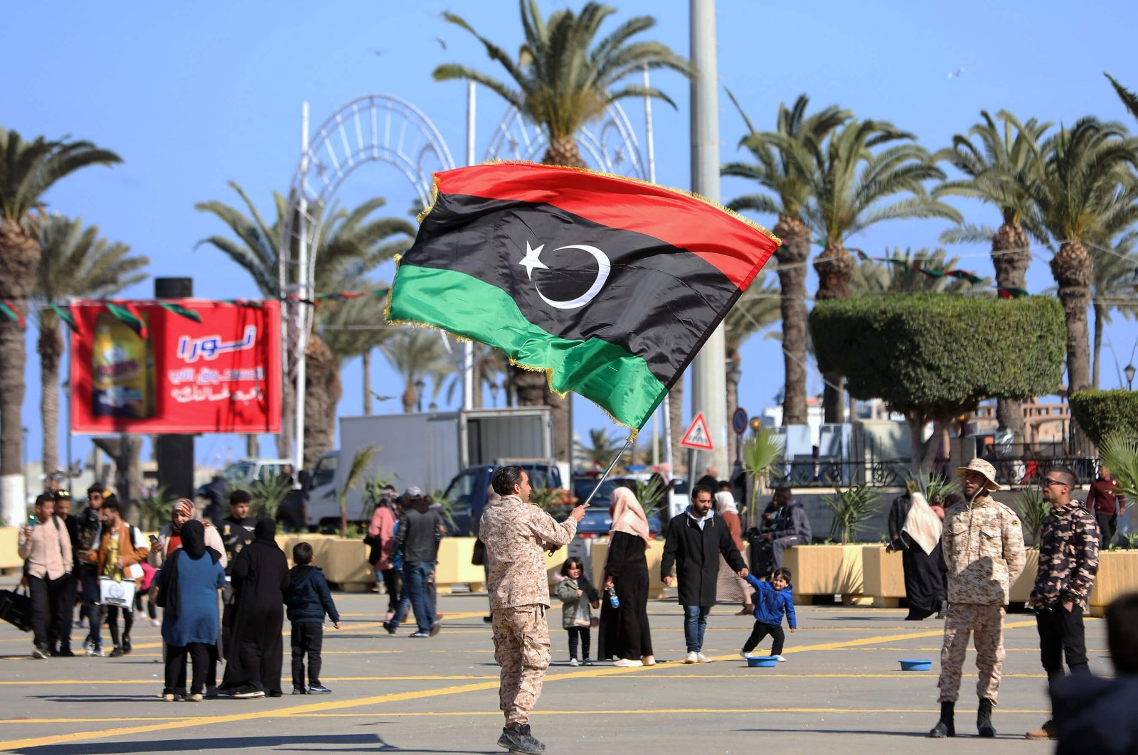 A soldier waves the Libyan flag a day ahead of the 10th anniversary of the country's Arab Spring uprising in Martyrs' Square, Tripoli, Libya. (AA Photo)