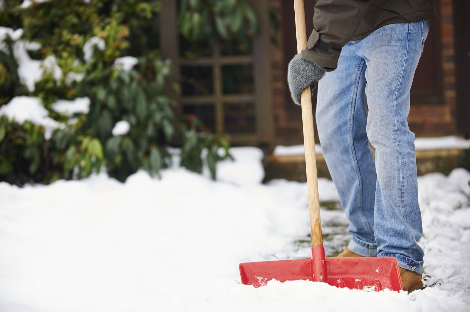 Trying to lift a shovel full of snow is asking for injury. (Shutterstock Photo)