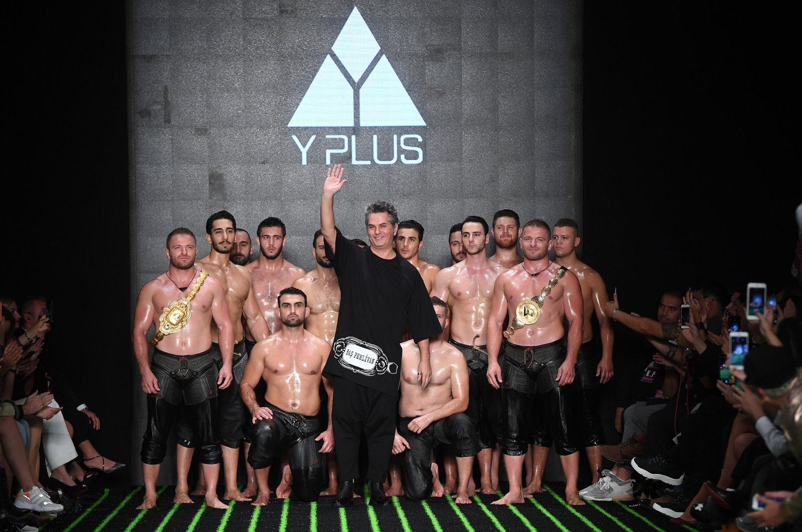 Designer Yakup Biçer (C) poses with Turkish wrestlers on the runway at the Y Plus By Yakup Bicer show during Mercedes-Benz Istanbul Fashion Week at Zorlu Performance Hall on October 9, 2019 in Istanbul, Turkey. (Getty Images for IHKIB)