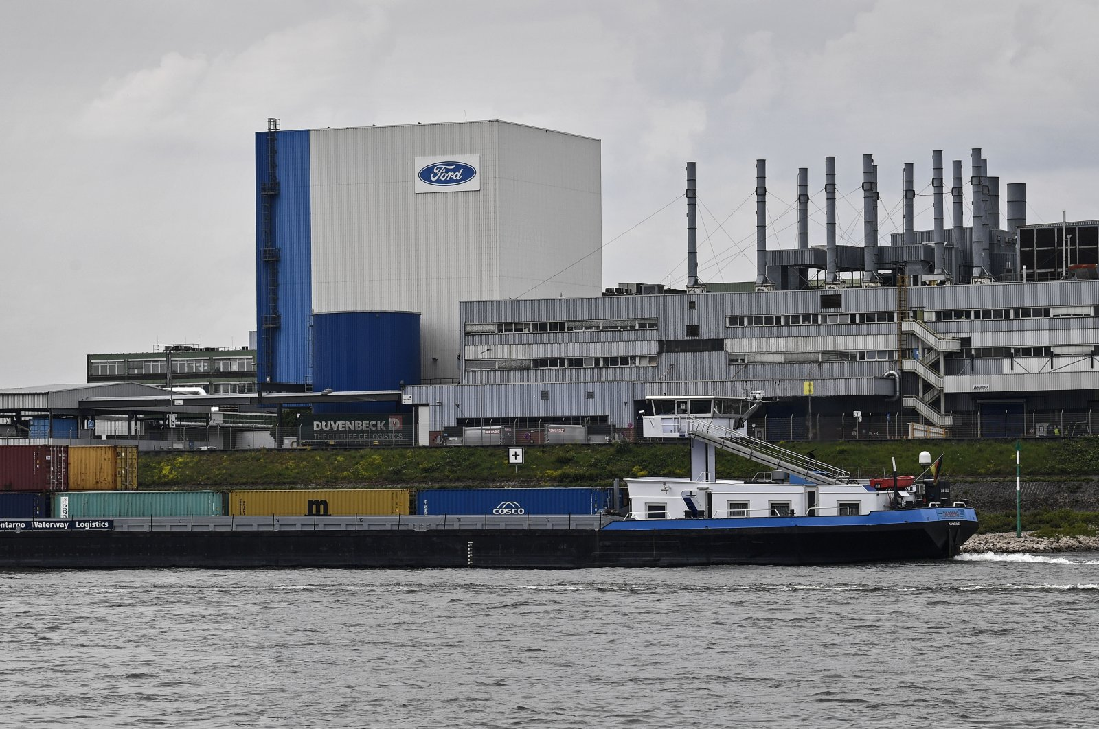 A container ship passes the Ford car plant in Cologne, Germany, May 4, 2020. (AP Photo)