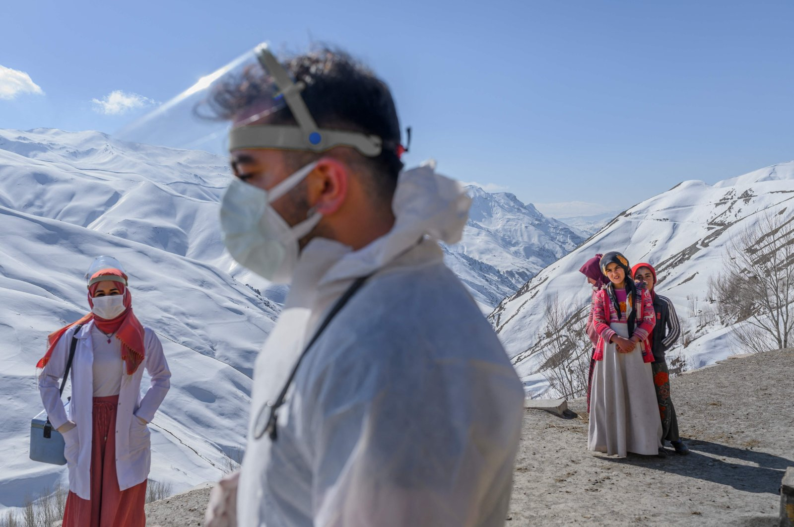 Doctor Sergen Saraçoğlu (C) and nurse Yıldız Ayten (L) from the Bahçesaray public hospital vaccination team arrive in the village of Güneyyamaç in Van province, eastern Turkey, Feb. 15, 2021, as part of an expedition to vaccinate residents of 65 years old or above with Sinovac's CoronaVac COVID-19 vaccine. (AFP Photo)