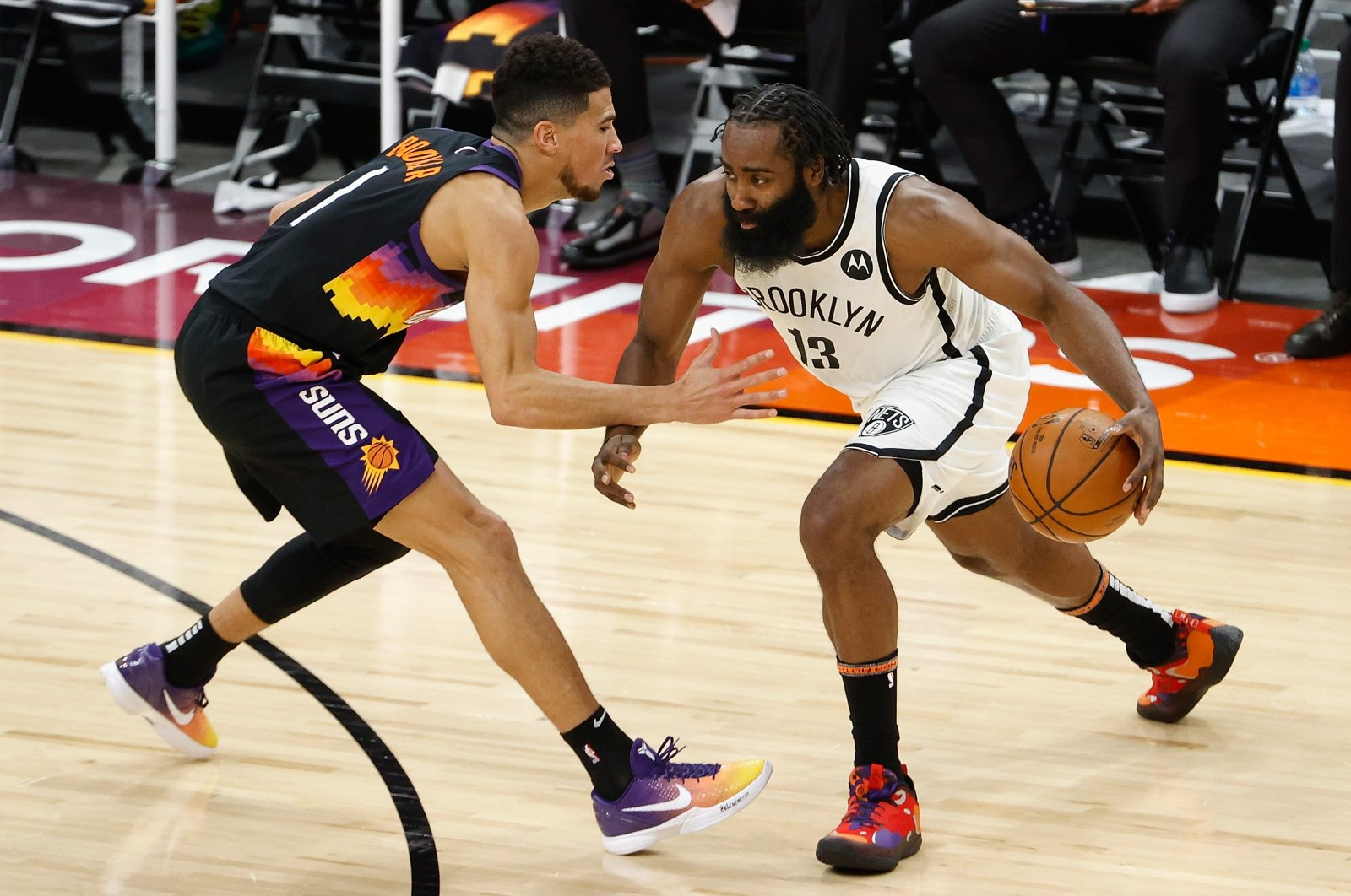 Brooklyn Nets' James Harden (R) drives the ball against Phoenix Suns' Devin Booker (L) during the second half of their NBA game at Phoenix Suns Arena, Phoenix, Arizona, Feb. 16, 2021. (AFP Photo)