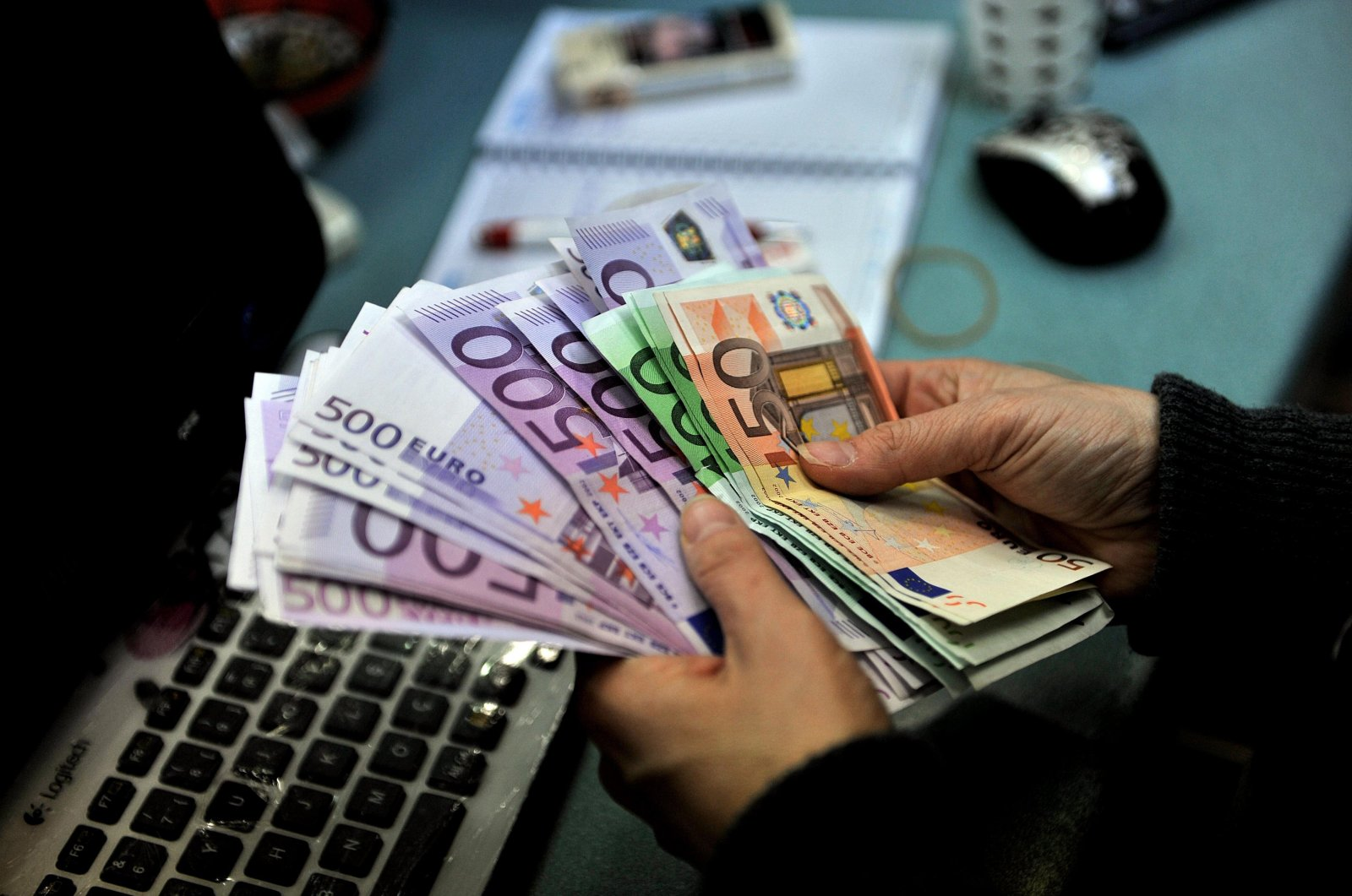 A person is seen counting money as Europe experiences a sharp rise in debt.