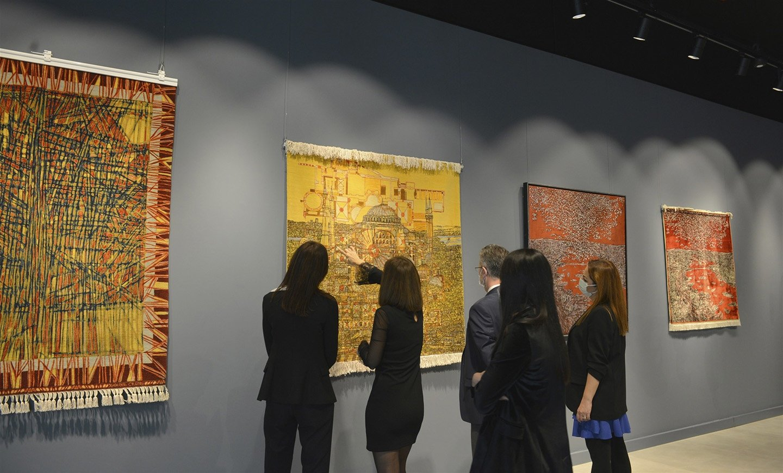 A group of visitors examines Devrim Erbil's unique artworks in the