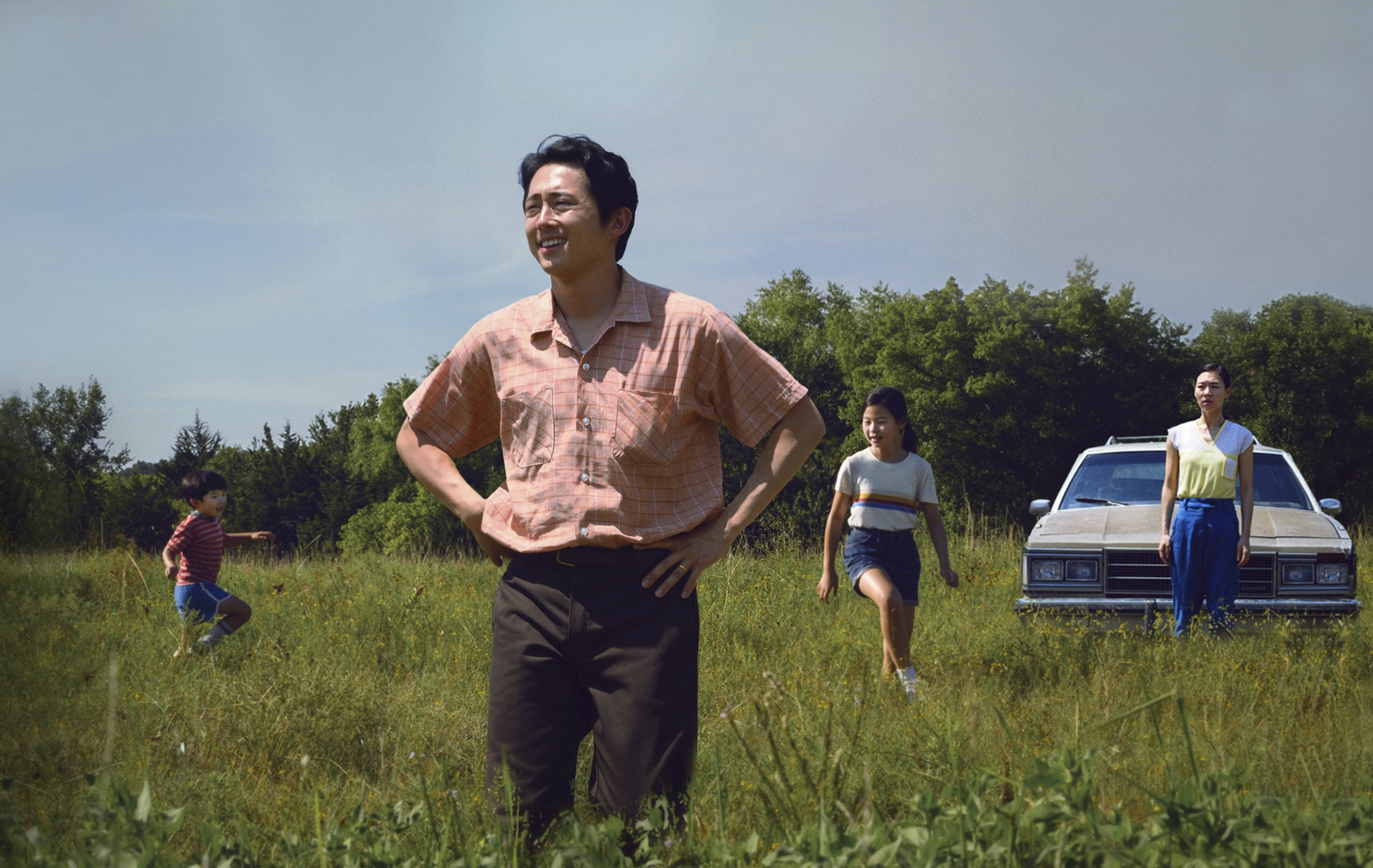 """A still image from the film """"Minari"""" shows Steven Yeun's character in the foreground, with his family in the background. (AP)"""