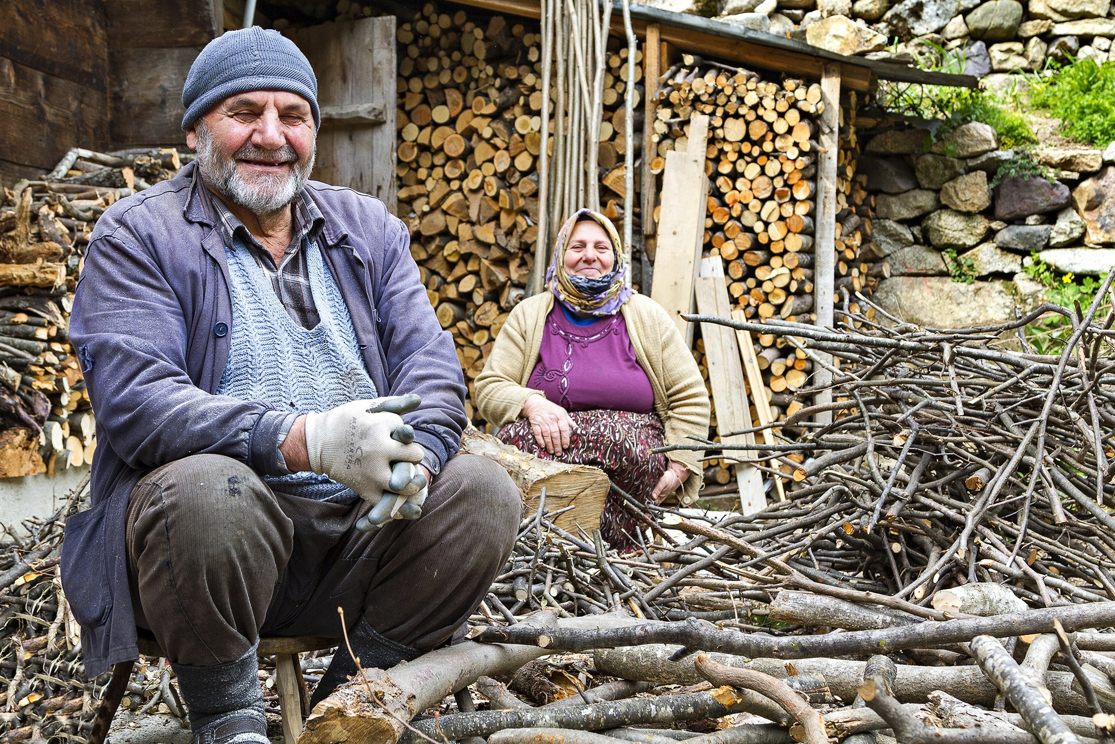 An elderly Turkish couple smiles at the camera while chopping firewood in Trabzon, Turkey,  April 2, 2014. (Shutterstock Photo)