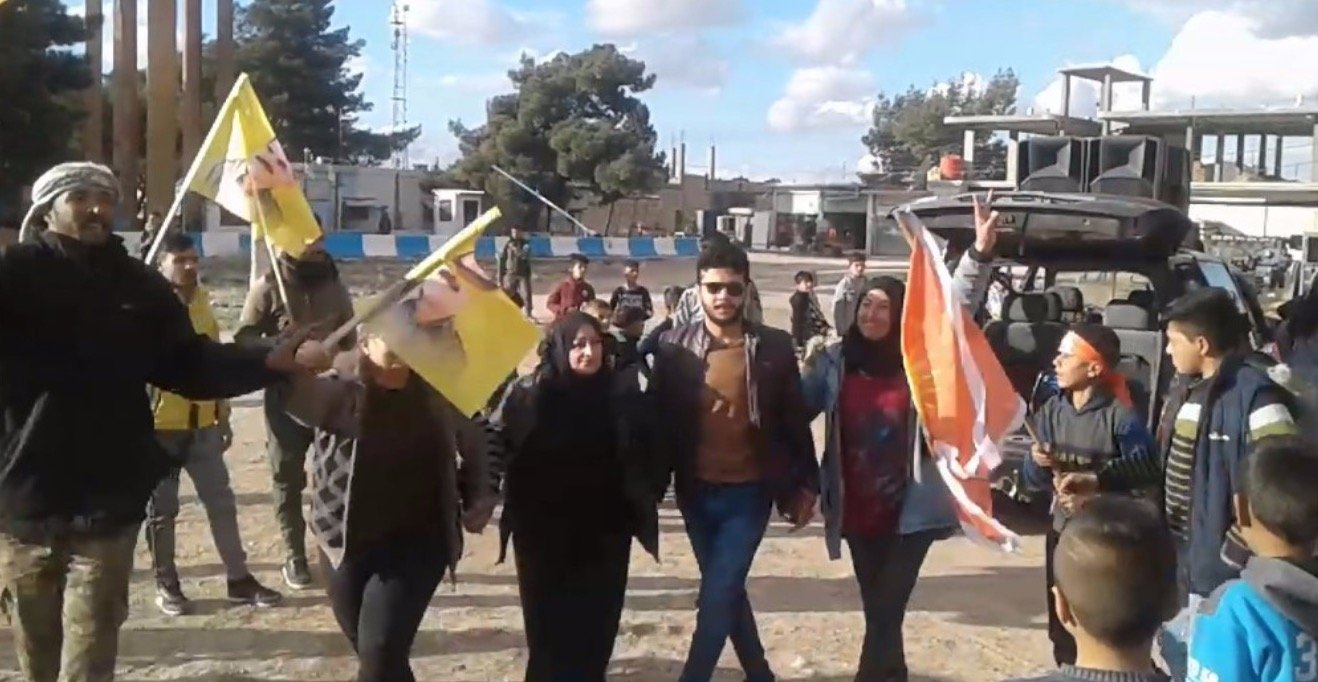 YPG sympathizers and militants wave banners of PKK leader Abdullah Öcalan in Syria's Al-Ya'rubiyah in celebration after the killing of 13 innocent Turkish citizens in northern Iraq's Gara on Feb. 18, 2021 (Screengrab from ANHA website)