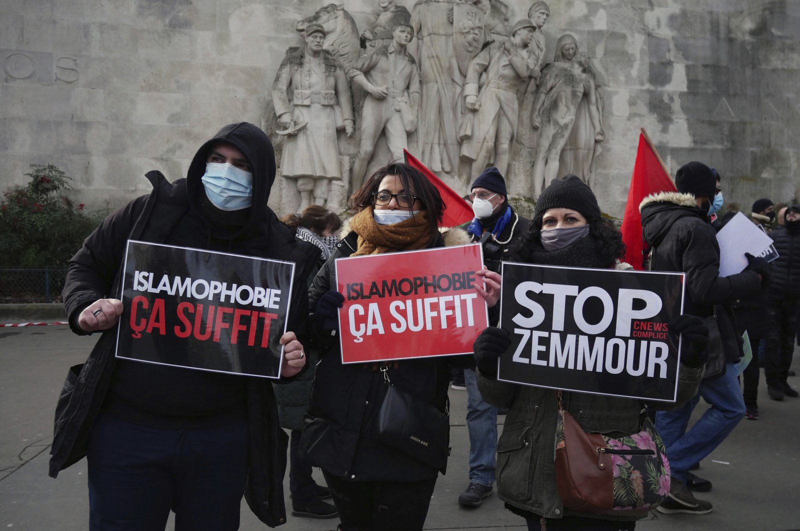 "Activists hold placards reading ""Islamophobia is enough"" and ""Stop Zemmour"" during a gathering in Paris, France, Feb. 14, 2021. (AP Photo)"