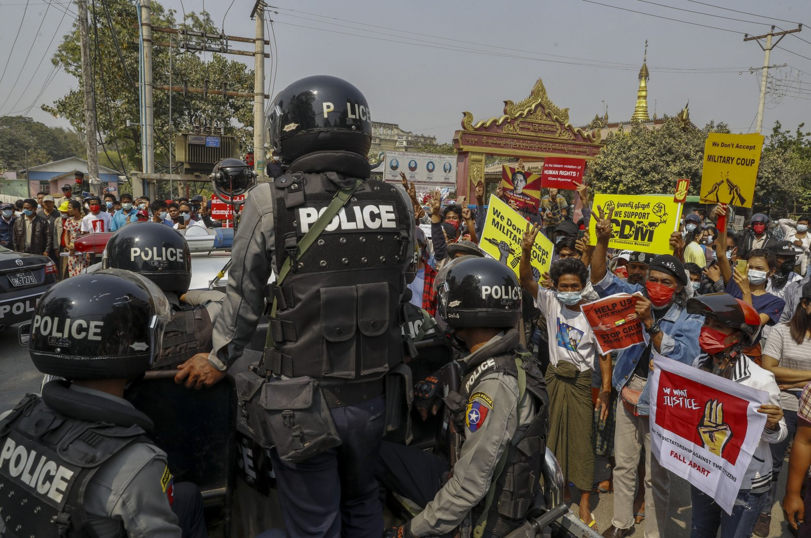 Police stand guard as demonstrators protest against the military junta's arrest and chagrining of National League for Democracy party lawmakers, Mandalay region Chief Minister Zaw Myint Maung & Mayor Ye Lwin outside Aung Myay Thar Zan Township court in Mandalay, Myanmar, Feb. 18, 2021. (AP Photo)