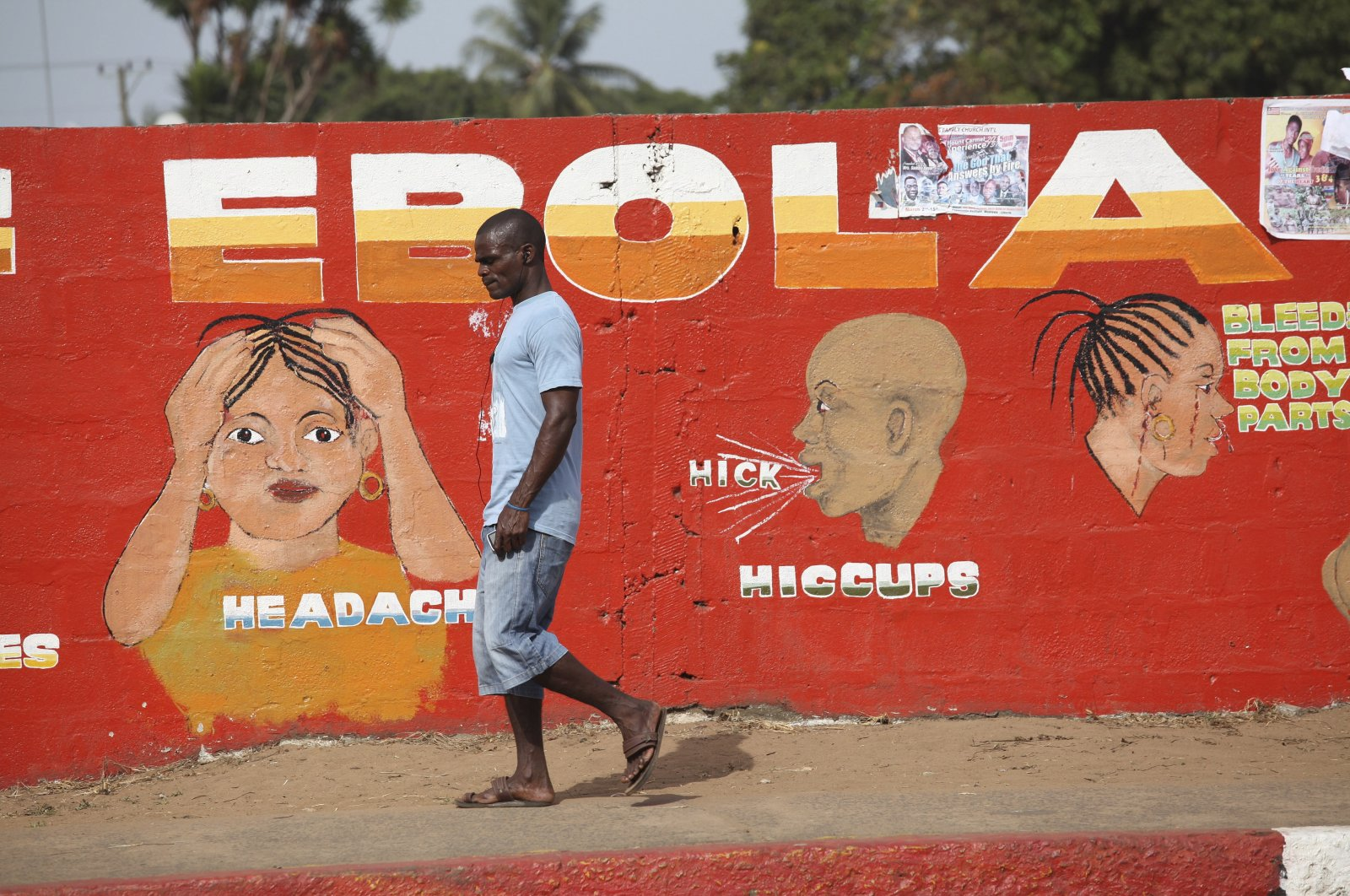 A Liberian man walks past an Ebola awareness painting on a wall in downtown Monrovia, Liberia, March 22, 2015. (EPA Photo)