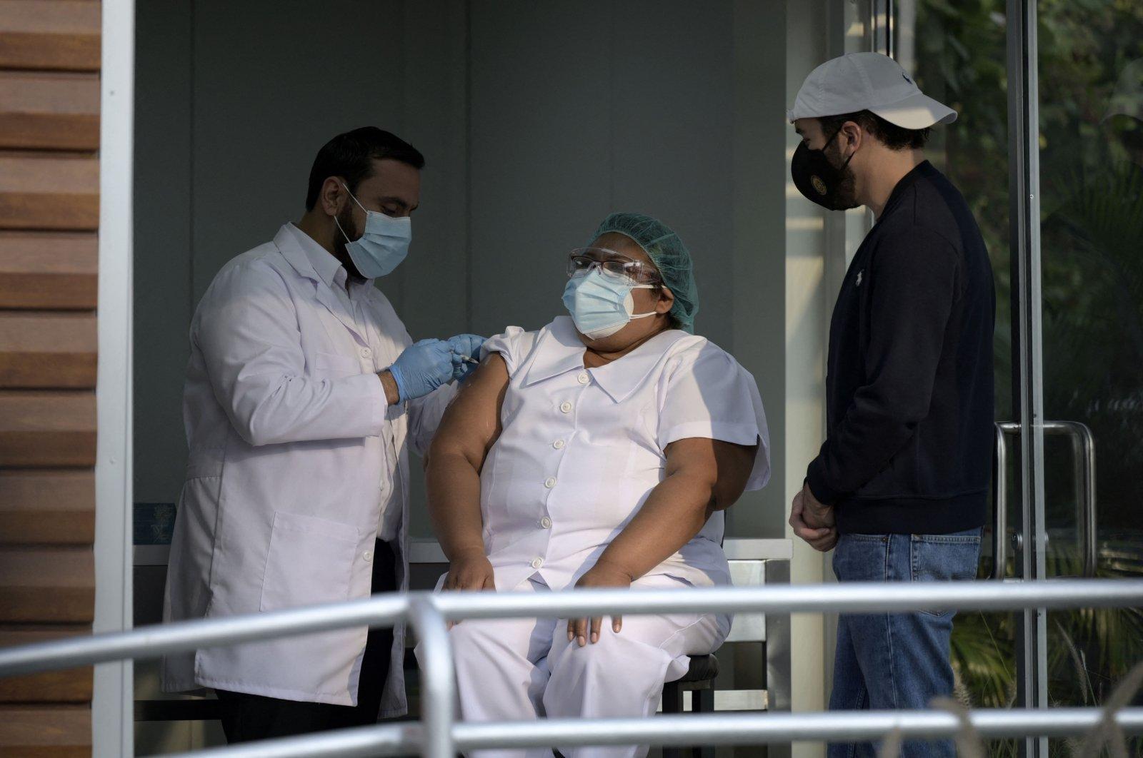 Salvadoran President Nayib Bukele (R) observes as Health Minister Francisco Alabi applies the first Oxford/AstraZeneca vaccine against COVID-19 to a health worker amid the novel coronavirus pandemic, in San Salvador, El Salvador, Feb. 17, 2021. (AFP Photo)