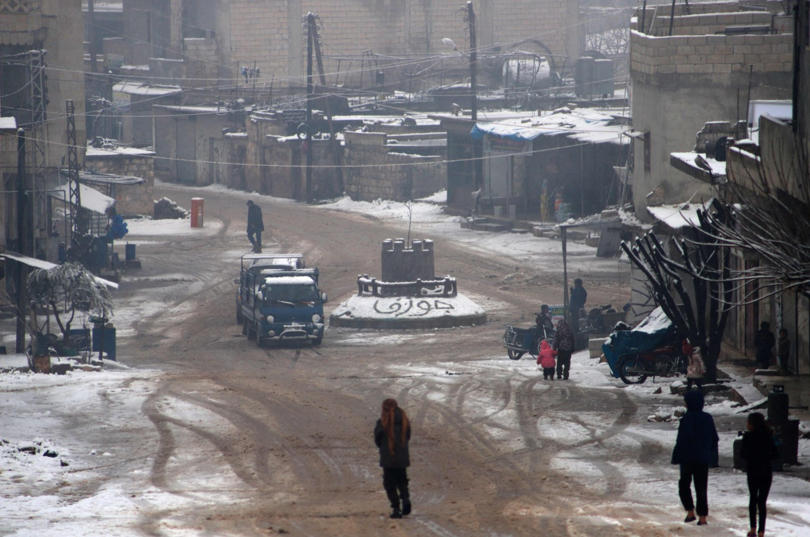 Snow covers a roundabout, with the town's name in Arabic drawn in the snow, as people walk in the town of Juzif on Zawiya Mountain of Syria's opposition-held Idlib province, Feb. 17, 2021. (AFP Photo)