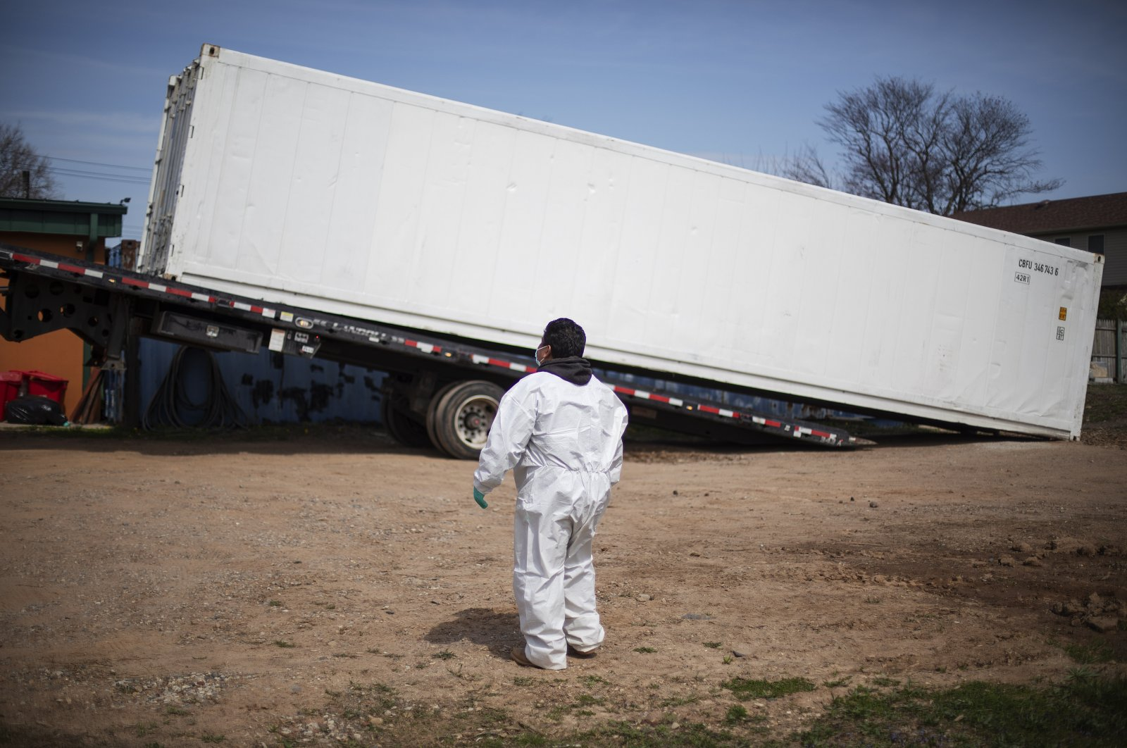 Gravedigger Thomas Cortez watches as a refrigerated trailer is delivered to keep pace with a surge of bodies arriving for burials, mostly those who died from coronavirus, at the Hebrew Free Burial Association's cemetery in the Staten Island borough of New York, U.S., April 7, 2020. (AP Photo)