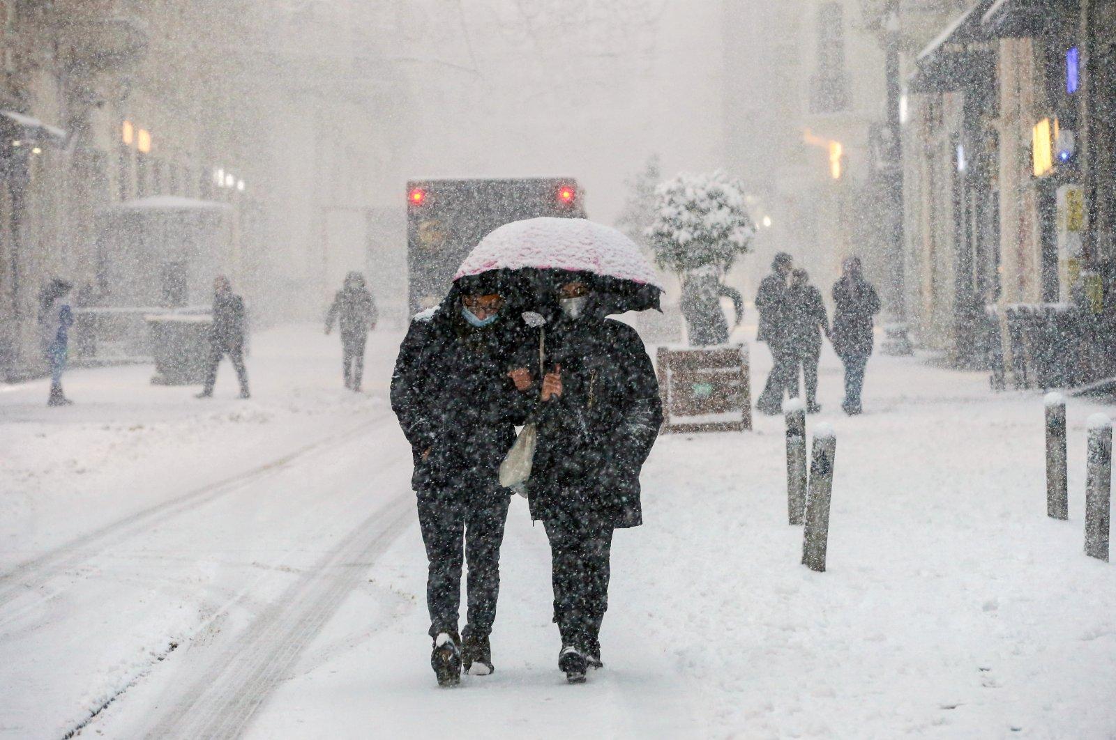 People walk along Istiklal Avenue as snow falls, in Istanbul, Turkey, Feb. 17, 2021. (AA Photo)