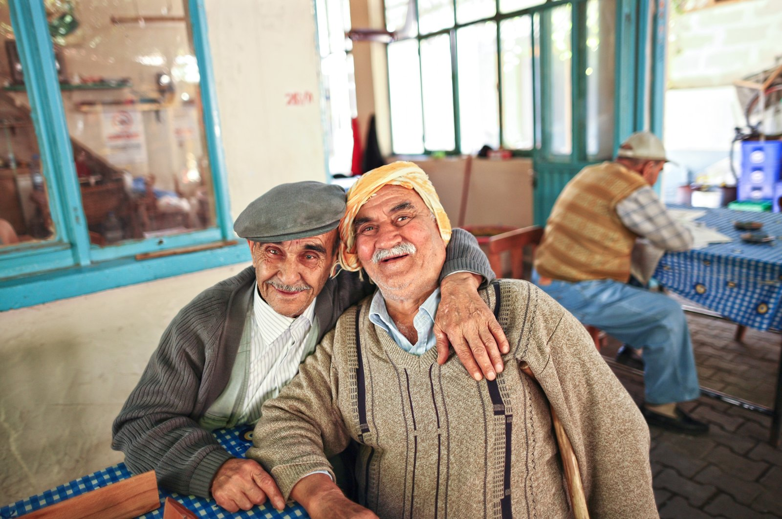 Two best friends hug each other in a traditional tea house in the Seferihisar district of Izmir, western Turkey, October 24, 2009. (Shutterstock Photo)