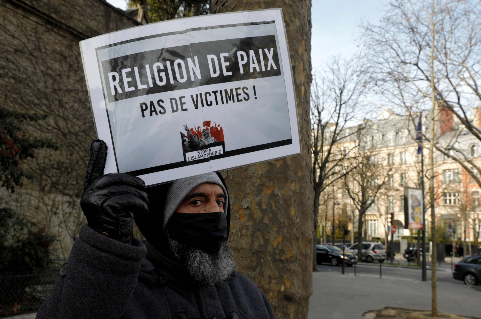 "A man holds a placard reading ""religion of peace"" as protesters demonstrate against a bill dubbed as ""anti-separatism,"" in Paris, France, Feb. 14, 2021. (AFP Photo)"