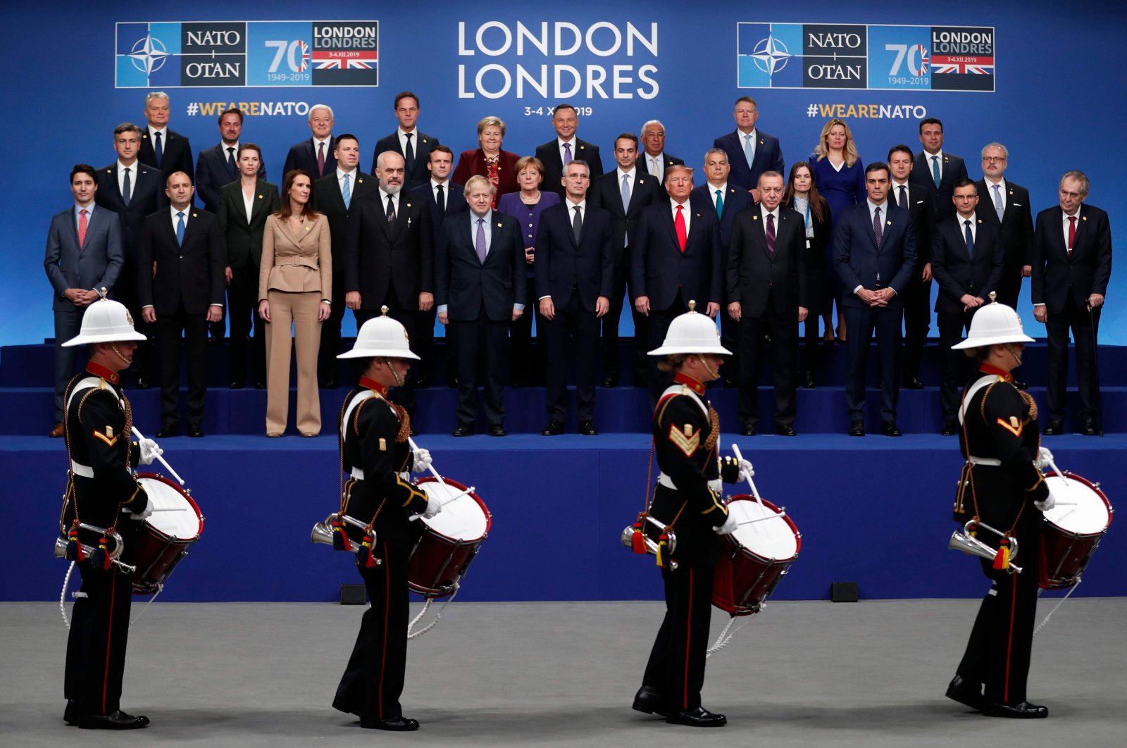 NATO heads of government watch a marching band perform as they pose for the family photo at the NATO summit at the Grove hotel in Watford, northeast of London on Dec. 4, 2019. (AFP)