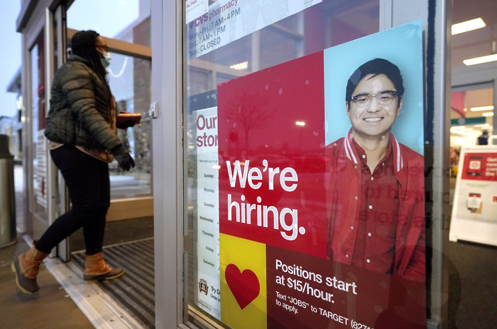 A passer-by walks past an employment hiring sign while entering a Target store location in Westwood, Mass., U.S., Feb. 9, 2021. (AP Photo)