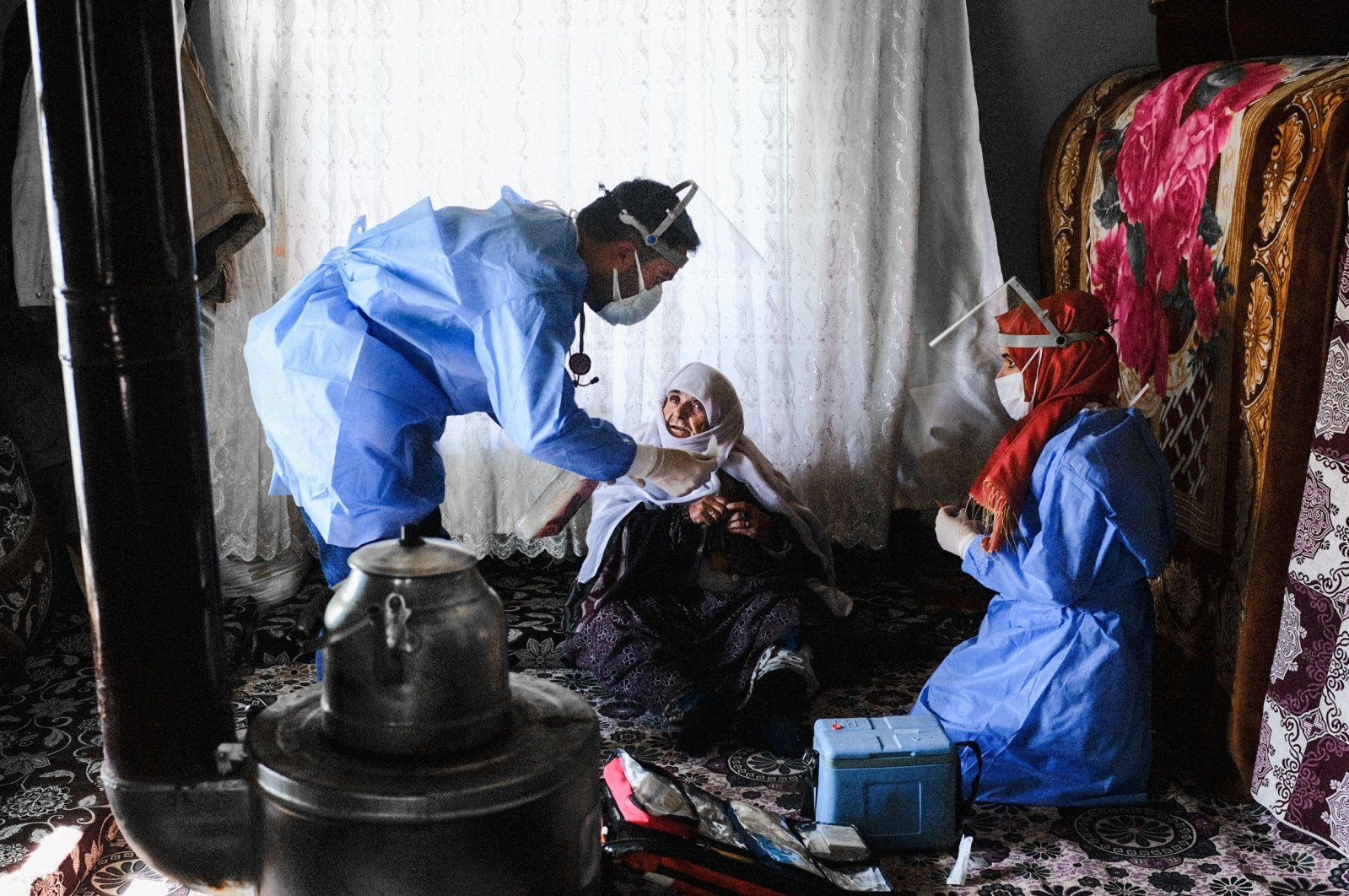 101-year-old Berfo Arsakay prepares to receive a vaccine from Doctor Akay Kaya (L) and nurse Yildiz Ayten (R) from the Bahçesaray public hospital vaccination team in the village of Güneyyamaç in eastern Turkey, Feb.15, 2021 (AFP Photo)