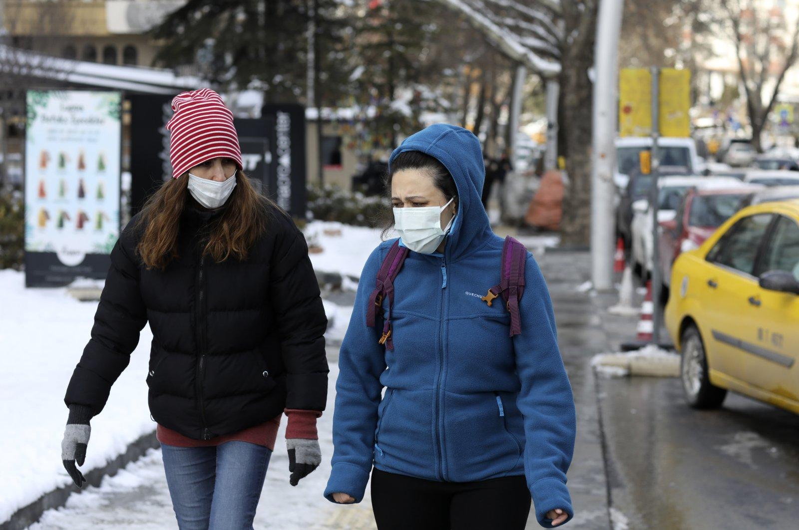 Women wearing masks walk along a busy street, in Ankara, Turkey, Feb. 17, 2021. (AP Photo)