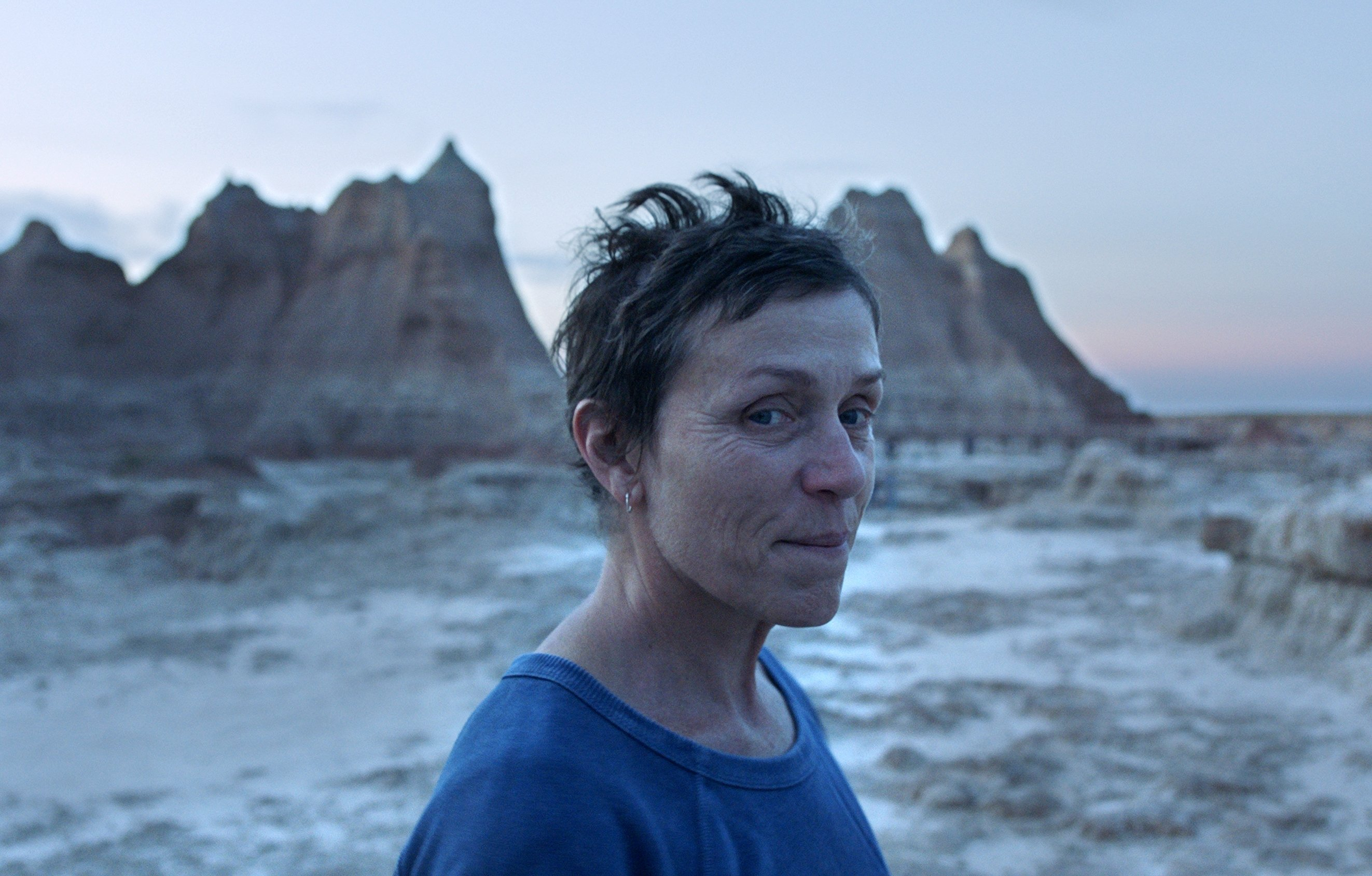 "A still image from the film ""Nomadland"" shows Frances McDormand looking into a distance. (Searchlight Pictures via AP)"