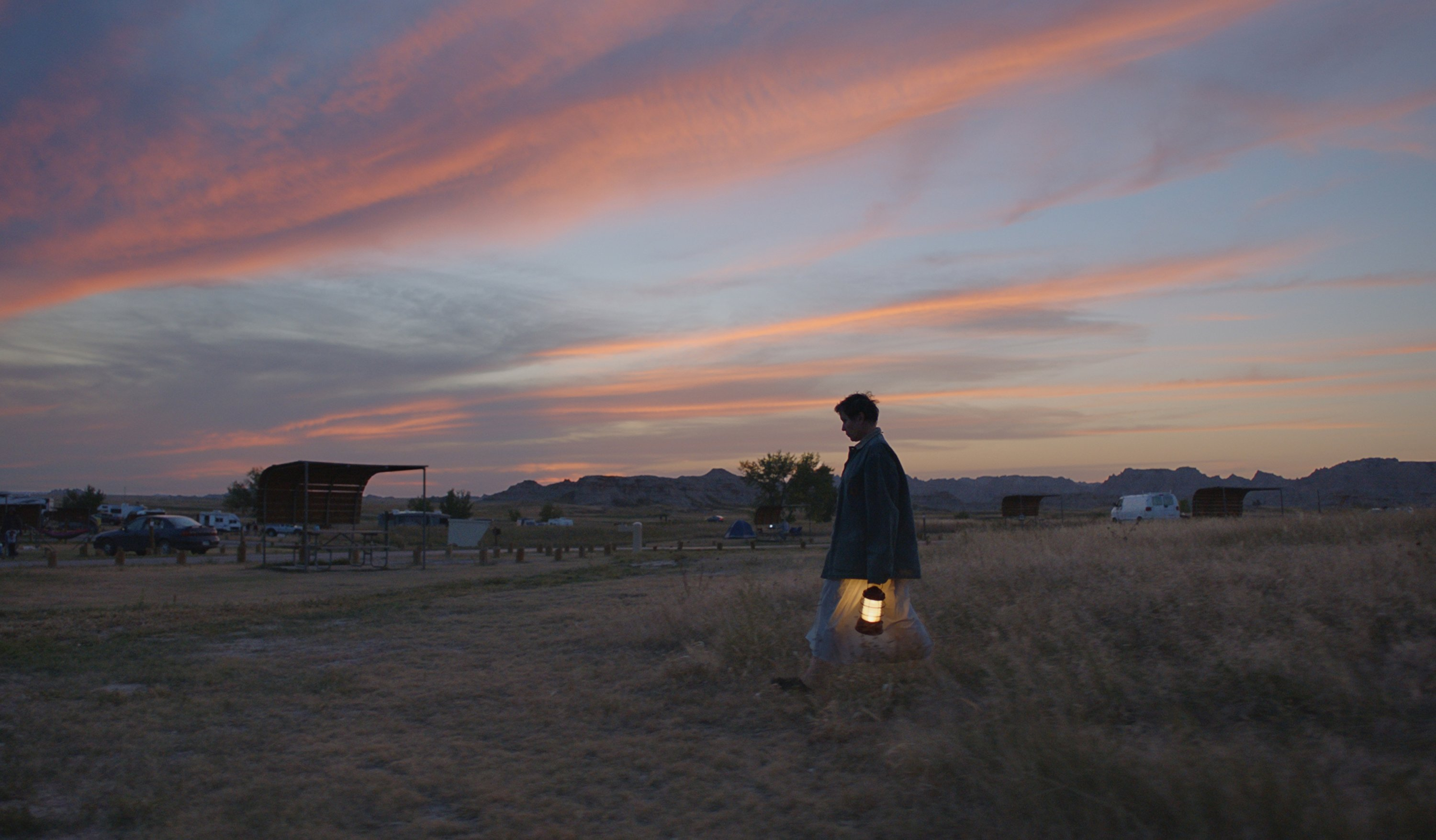 "A still image from the film ""Nomadland"" shows Frances McDormand walking in a field holding a lantern. (Searchlight Pictures via AP)"