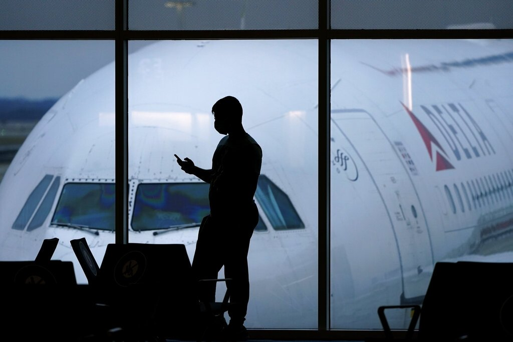 A passenger wears a face mask to help prevent the spread of the new coronavirus as he waits for a Delta Airlines flight at Hartsfield-Jackson International Airport in Atlanta, Thursday, Feb. 18, 2021. (AP Photo)