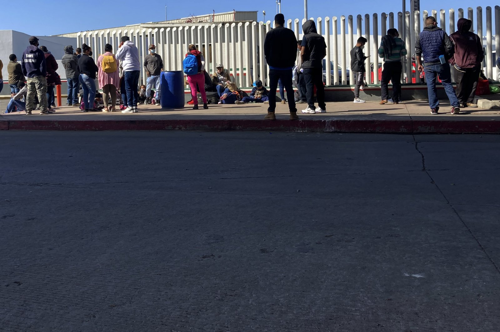 Migrants waiting to cross into the United States wait for news at the border crossing Wednesday, Feb. 17, 2021, in Tijuana, Mexico. (AP Photo)
