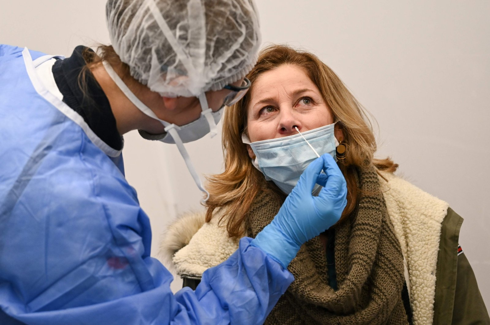 A medical worker uses a swab to perform a diagnostic PCR test for COVID-19 on an arriving passenger at a testing booth in Roissy-Charles de Gaulle Airport, north-east of Paris, France, Feb. 13, 2021. (AFP Photo)