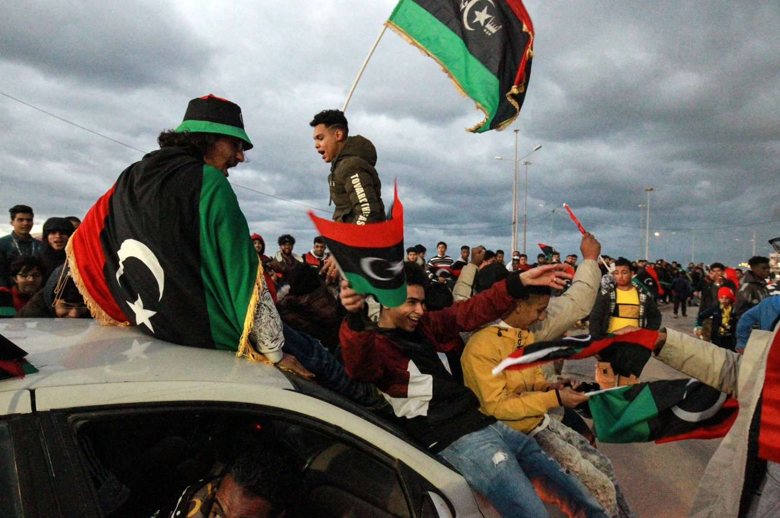 Libyans wave national flags as they gather to mark the 10th anniversary of the 2011 revolution, in the eastern city of Benghazi, Libya, Feb. 17, 2021. (AFP Photo)
