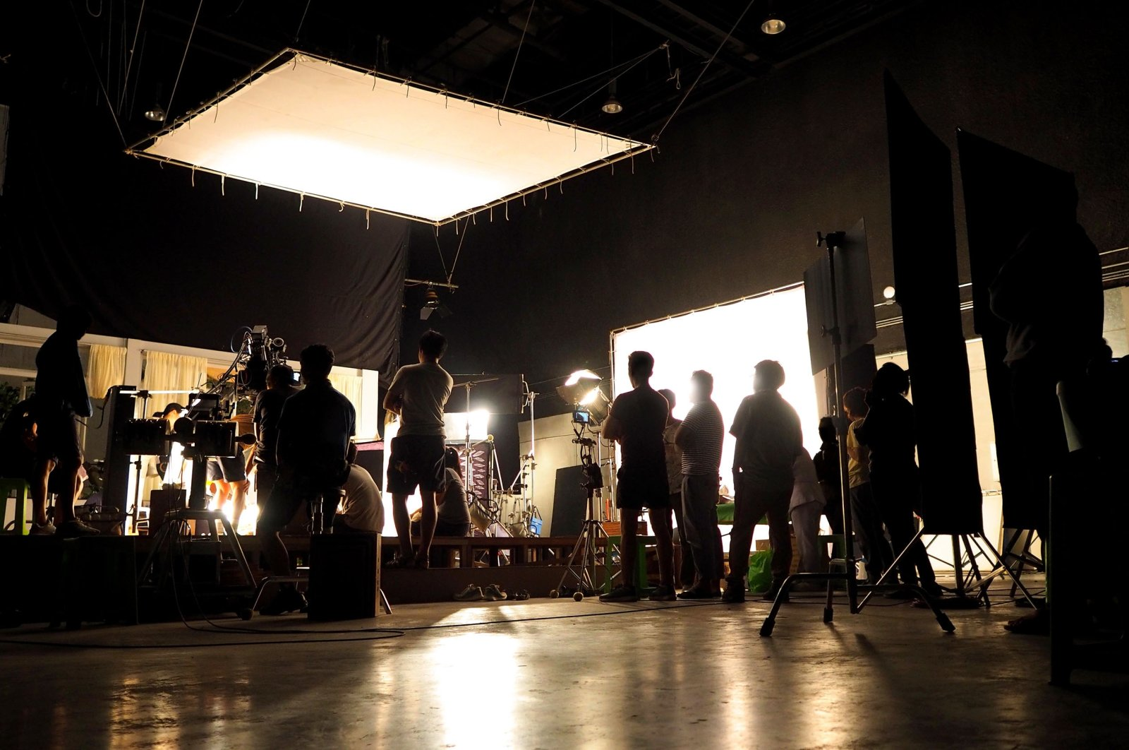A film crew's silhouettes and equipment can be seen behind the scenes of a video production. (Shutterstock Photo)