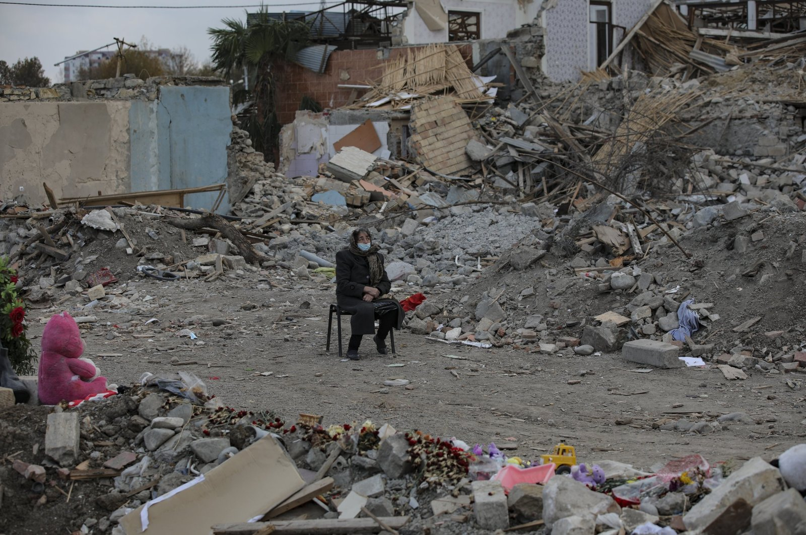 An Azerbaijani citizen sits in front of the ruins of her home, destroyed by rocket fire from Armenian forces, in Ganja, Azerbaijan, Nov. 28, 2020. (AP Photo)