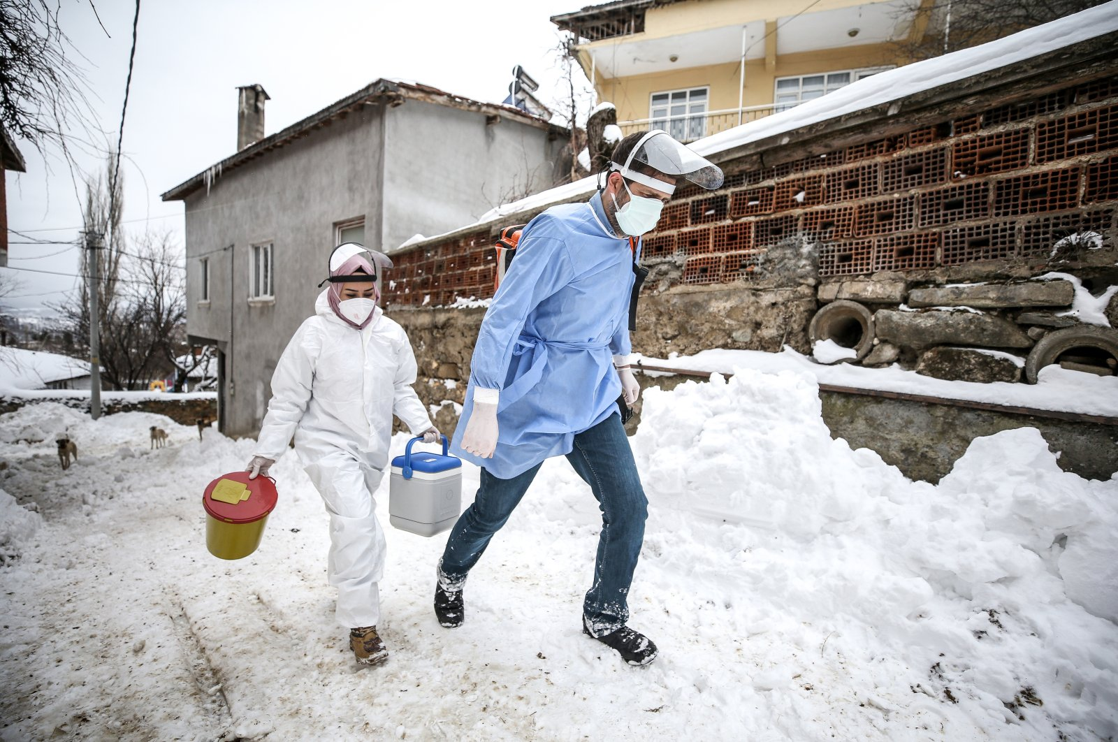 Health care workers walk on a snow-covered street to vaccinate people at home, in Bursa, northwestern Turkey, Feb. 19, 2021. (AA Photo)