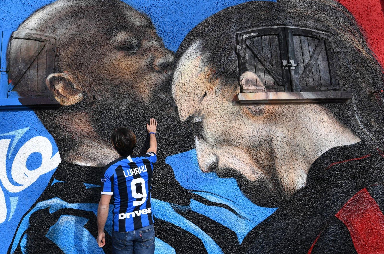 An Inter supporter touches a mural near the Giuseppe Meazza Stadium, depicting Inter Milan's Romelu Lukaku (L) and AC Milan's Zlatan Ibrahimovic during an Italian Cup match, in Milan, Italy, Feb. 15, 2021. (EPA Photo)