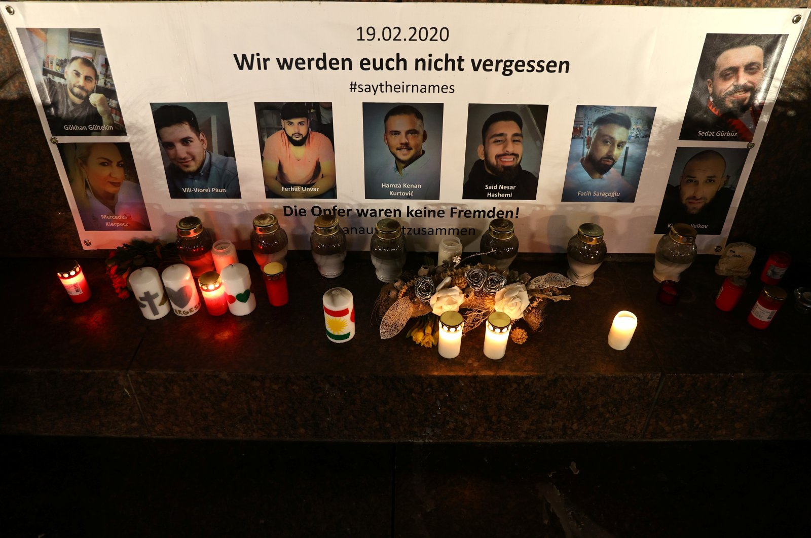 Pictures of the victims and candles are seen at the statue of German writers brothers Grimm one night ahead of the first anniversary of an attack where a man, who had posted a racist manifesto online, shot dead nine people in Hanau, Germany, Feb. 18, 2021.  (Reuters Photo)