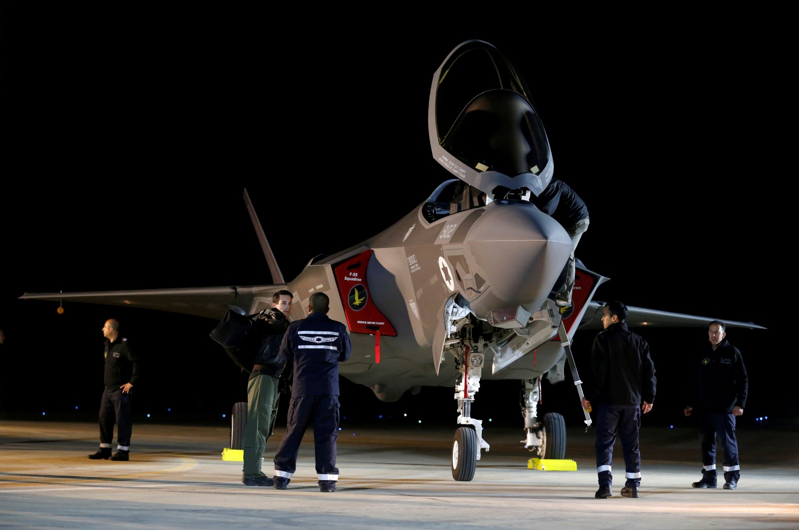 Israeli soldiers walk near an F-35 fighter jet, purchased by the Israeli Air Force, after it landed at Nevatim Air Base, in Nevatim, southern Israel, Dec. 12, 2016. (Reuters Photo)