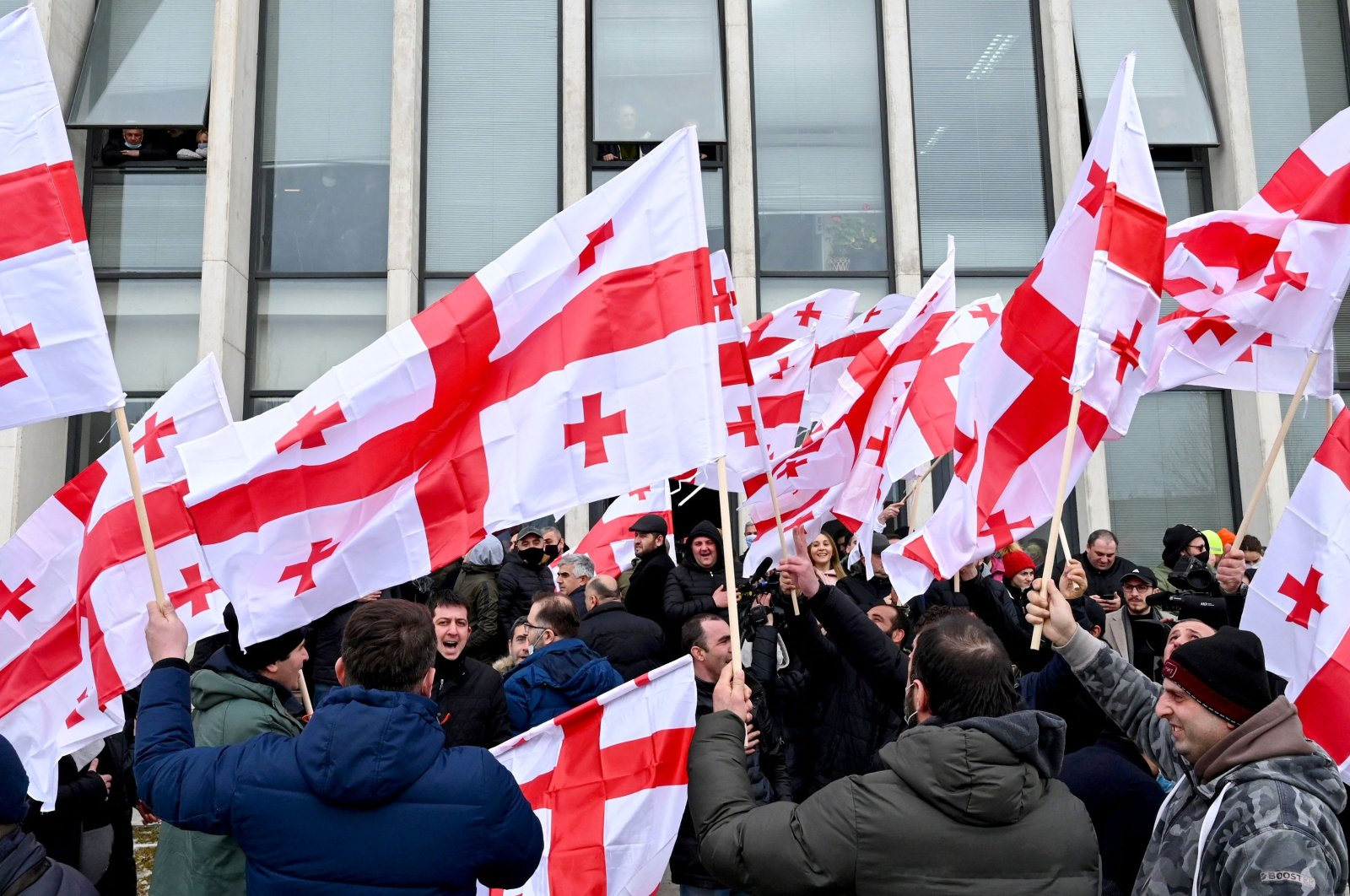 Georgian opposition supporters wave national flags while reacting to the announcement of Prime Minister Giorgi Gakharia's resignation in front of the United National Movement (UNM) headquarters in Tbilisi, Georgia, Feb. 18, 2021. (AFP Photo)