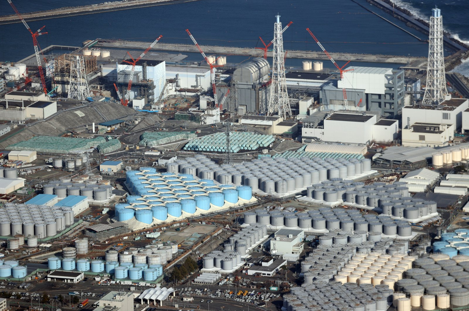 An aerial view shows tanks containing contaminated water and the Fukushima Daiichi nuclear power plant which suffered meltdowns on 11 March 2011, in Fukushima prefecture, northeastern Japan, Feb. 14, 2021. (EPA Photo)