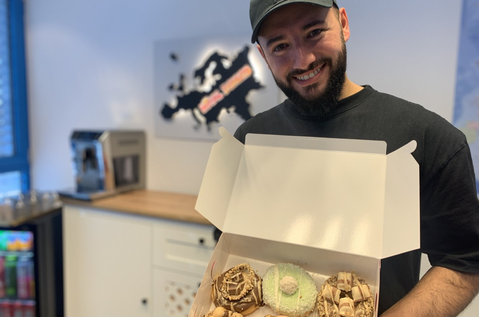 Enes Şeker shows a box of Royal Donuts in one of his stores in this photo provided on Feb. 19, 2021. (DHA Photo)