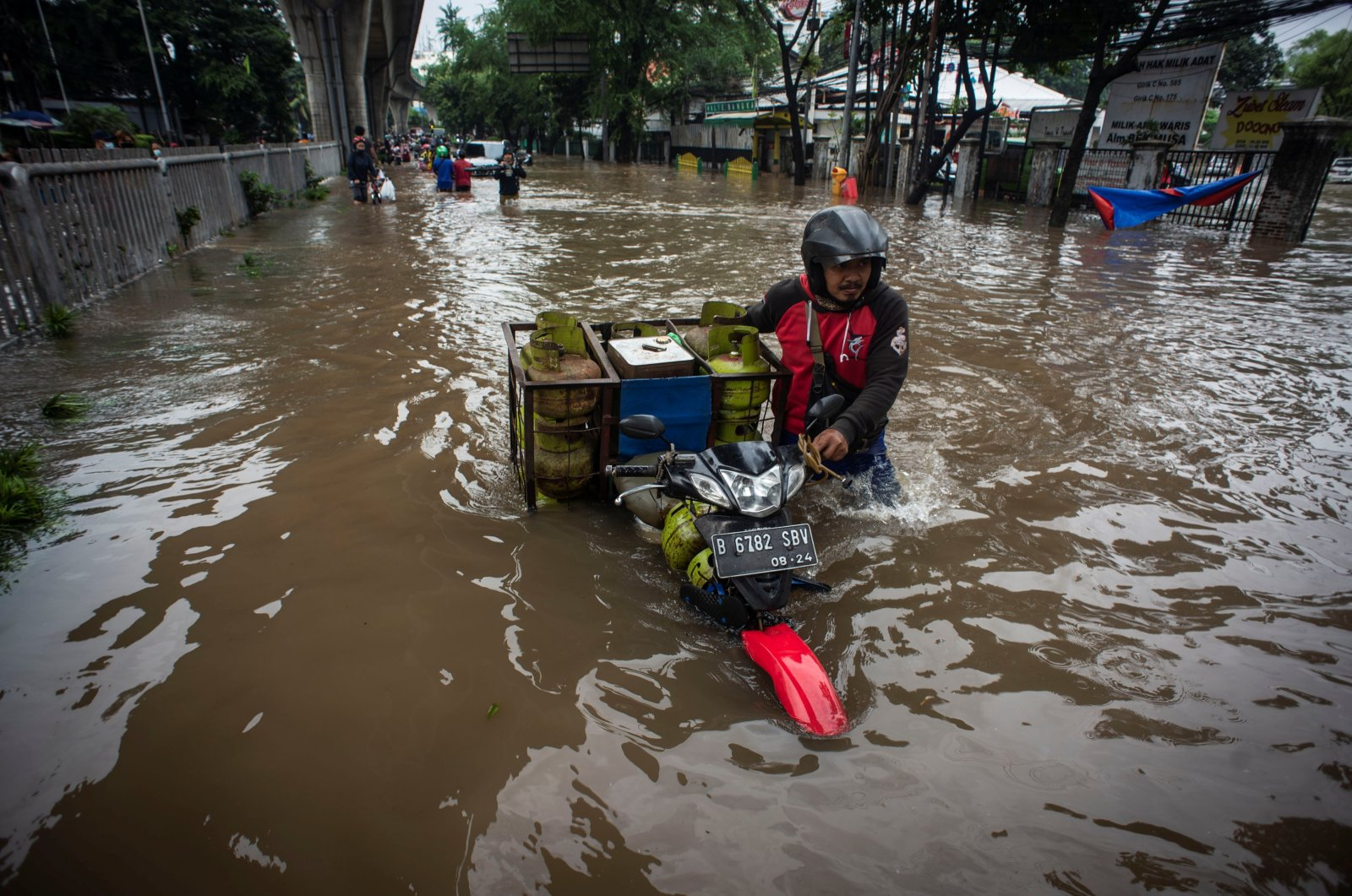 Man pushes his motorbike through water in an area affected by floods following heavy rains in Jakarta, Indonesia, Feb. 20, 2021. (Reuters Photo)