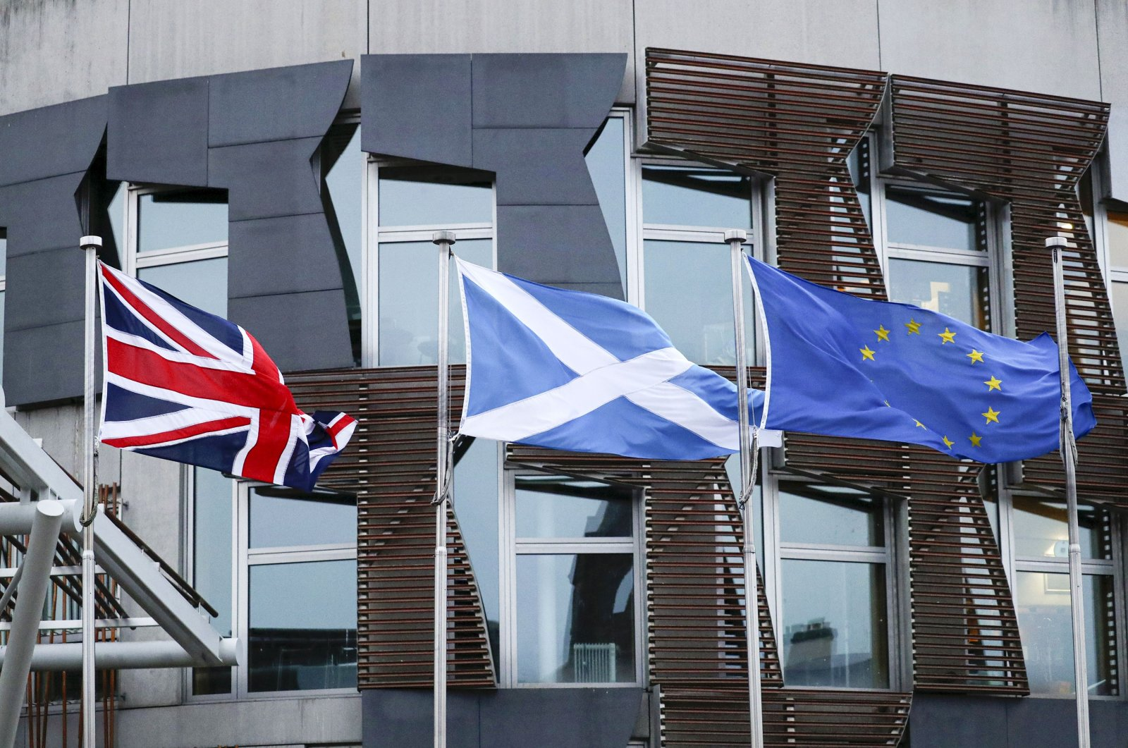 From left, the flags of Britain, Scotland and European Union wave outside the Scottish parliament in Edinburgh, Jan. 31, 2020. (AP Photo)