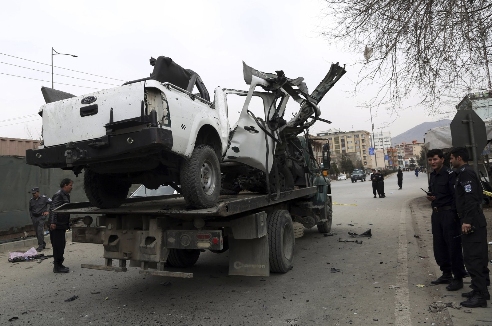 Afghan security personnel removes a damaged vehicle from the site of a bomb attack in Kabul, Afghanistan, Feb. 20, 2021. (AP Photo)