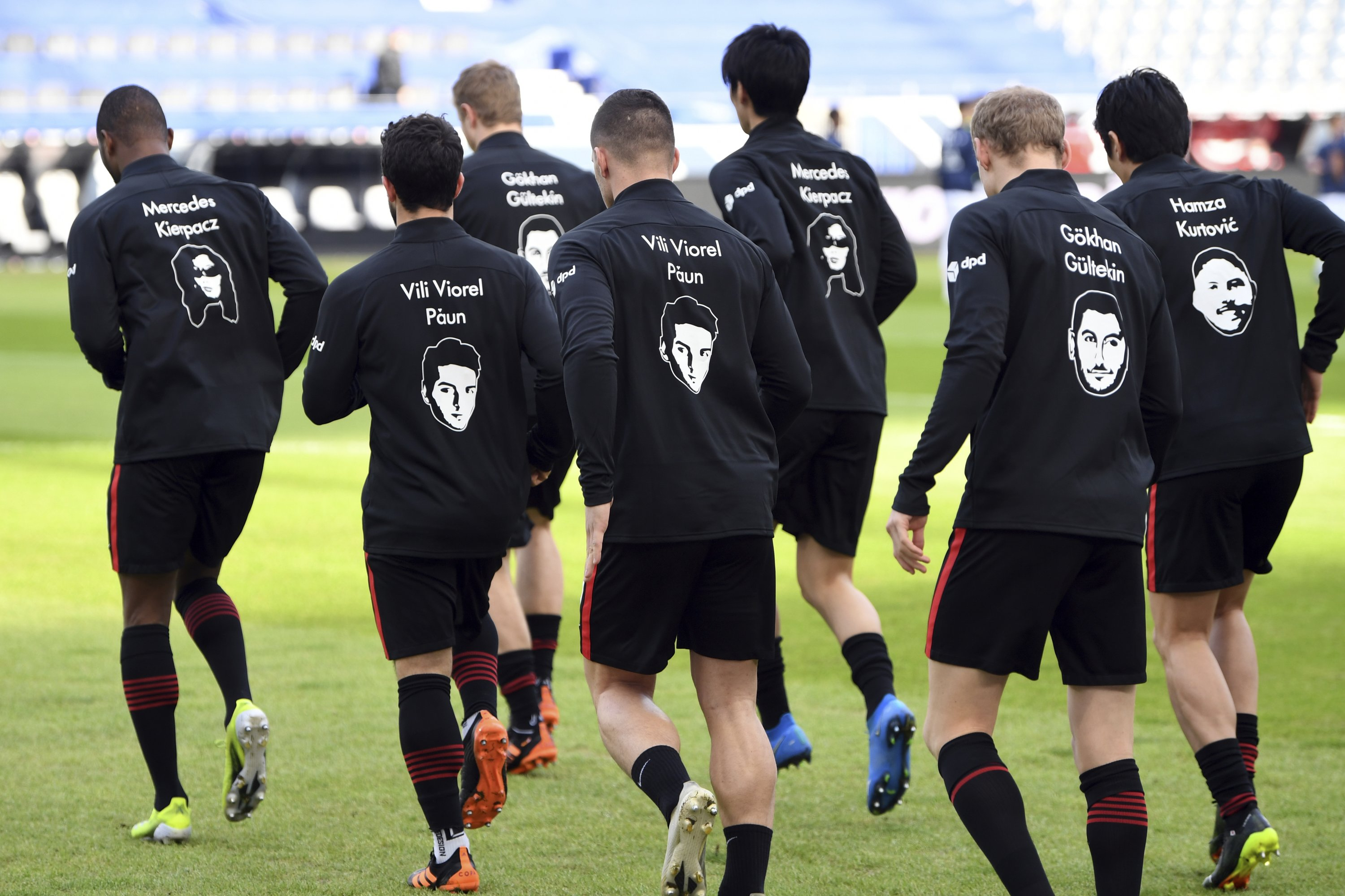 Frankfurt players wear the pictures and names of the victims of the shooting in Hanau a year ago on their training jackets, prior to the German Bundesliga match against Bayern Munich, Frankfurt, Germany, Feb. 20, 2021. (AP Photo)