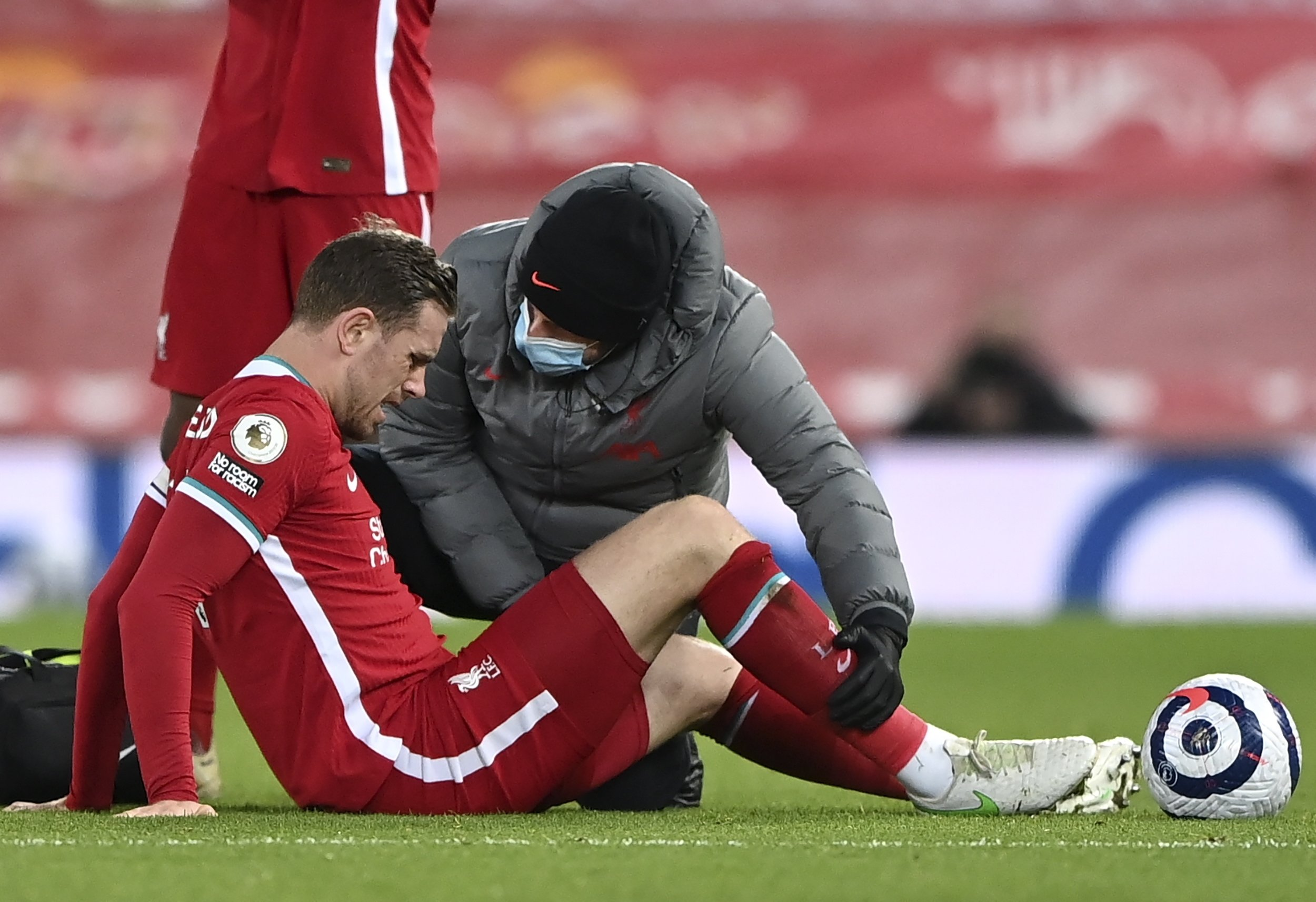 Liverpool's Jordan Henderson (L) receives medical assistance after picking up an injury during the English Premier League match against Everton, Liverpool, Britain, Feb. 20, 2021. (EPA Photo)
