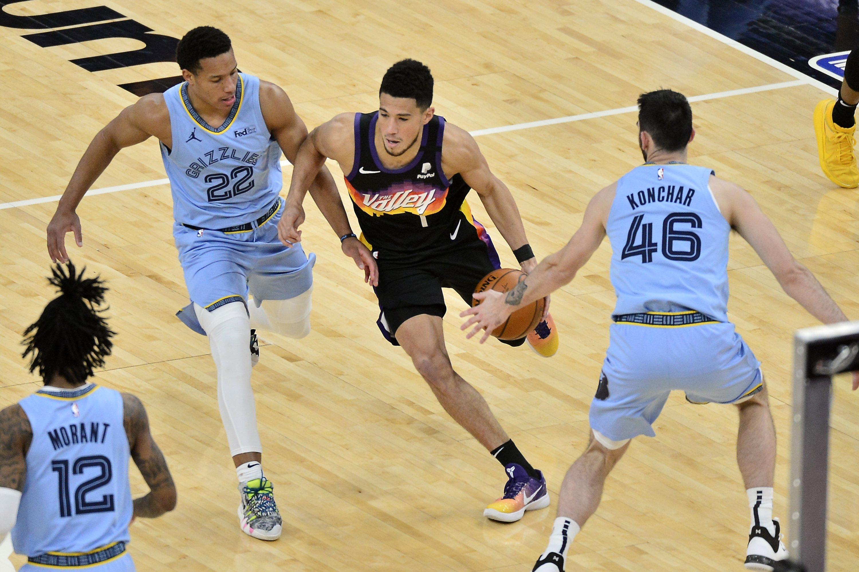 Phoenix Suns guard Devin Booker (C) handles the ball against Memphis Grizzlies guards Desmond Bane (L) and John Konchar (R) in an NBA game, in Memphis, Tennesse, Feb. 20, 2021. (AP Photo)