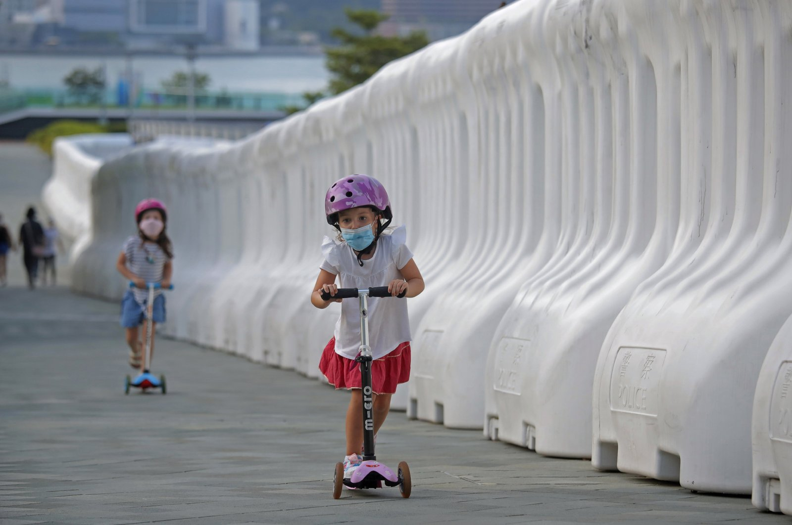 Kids wearing masks to protect against the coronavirus, play beside the water-filled barriers outside the Hong Kong Government Office in Hong Kong, Thursday, Aug. 20, 2020. (AP Photo)
