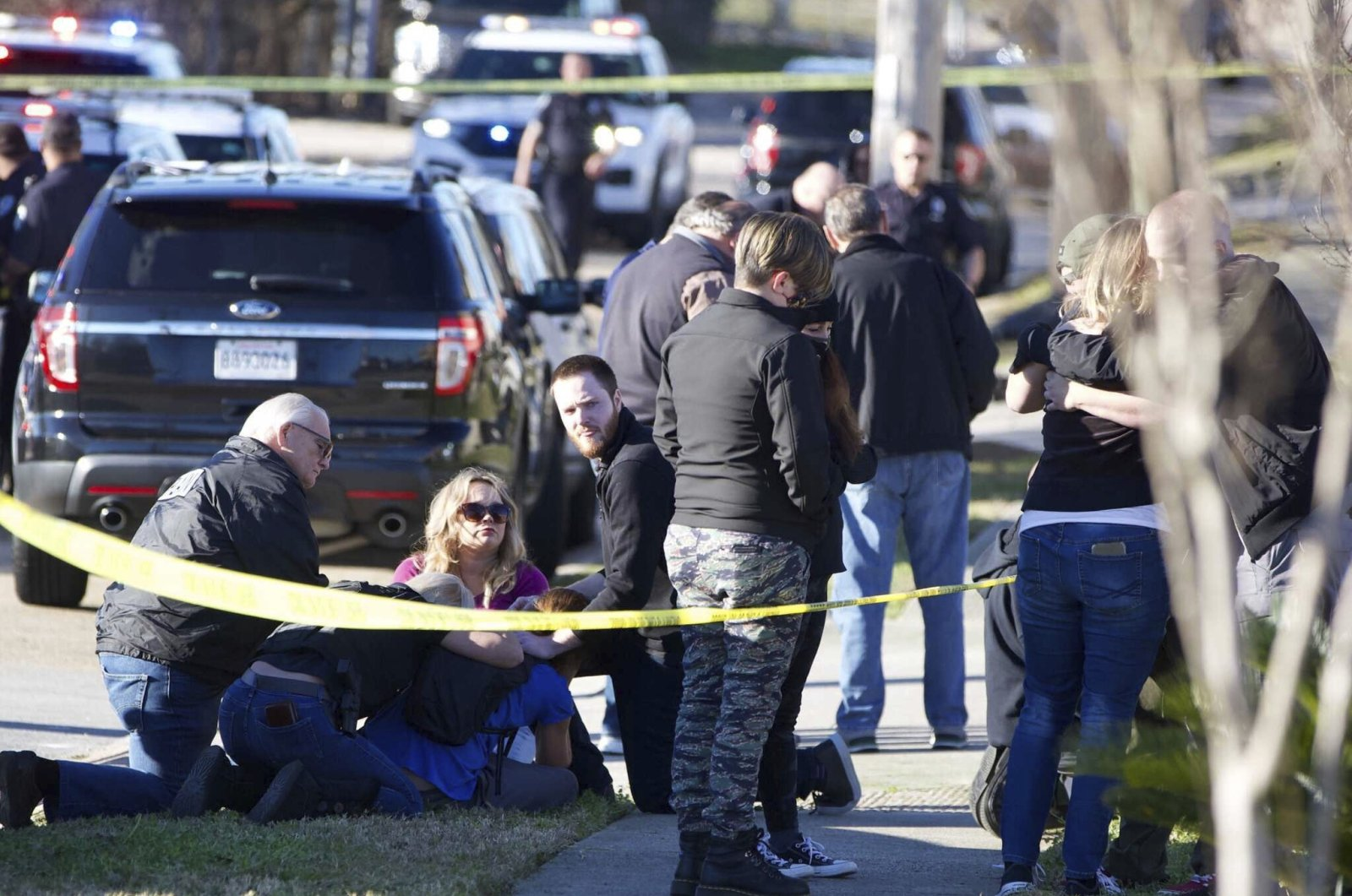People are comforted by law enforcement as the Jefferson Parish Sheriff's Office deputies investigate a shooting at the Jefferson Gun Outlet in Metairie, Louisiana, U.S., Feb. 20, 2021. (AP Photo)