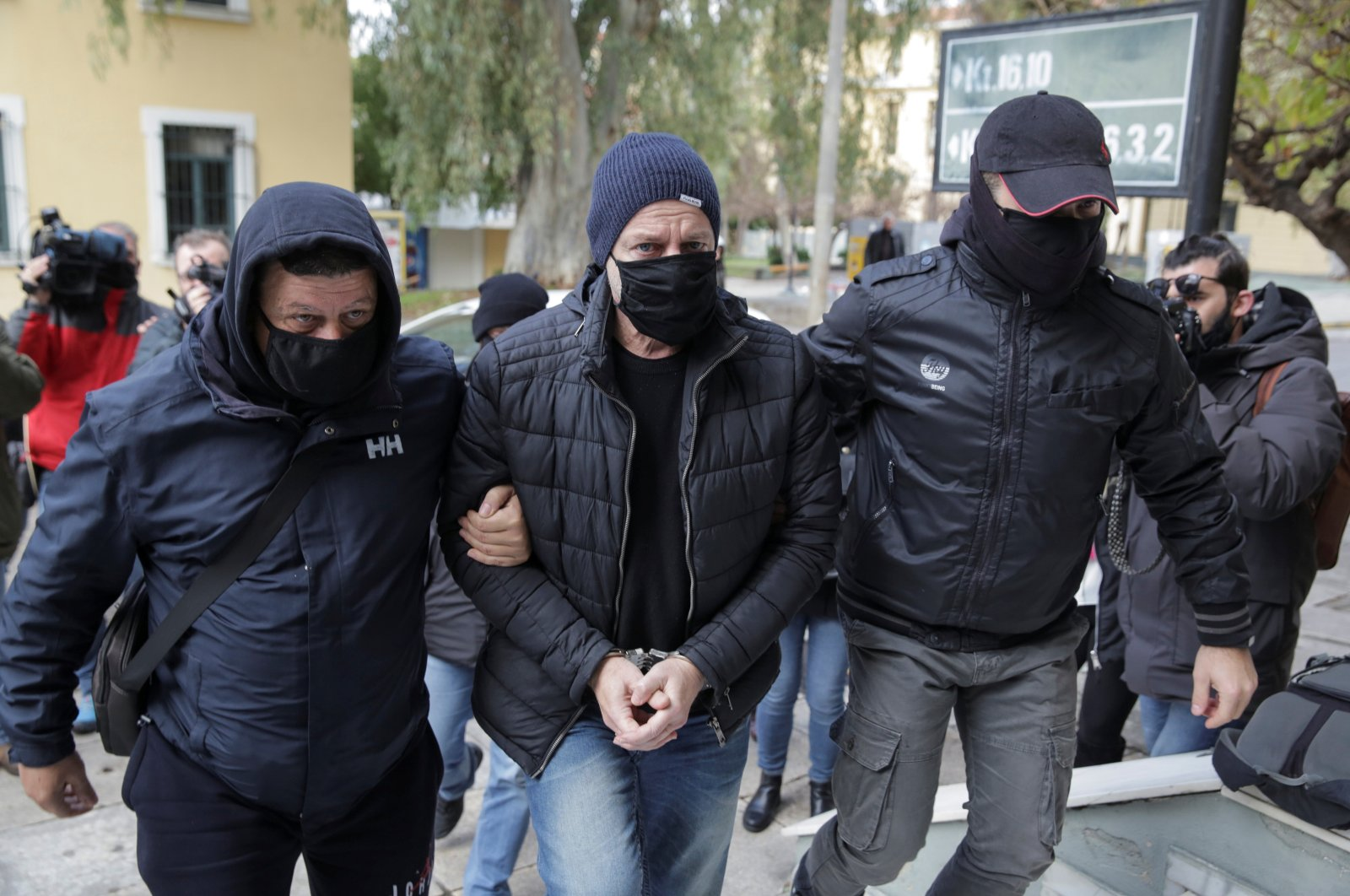 Greek actor and former director of Greece's National Theatre Dimitris Lignadis is escorted by plain clothes police officers as he enters the prosecutor's office in Athens, Greece, Feb. 21, 2021. (Reuters Photo)
