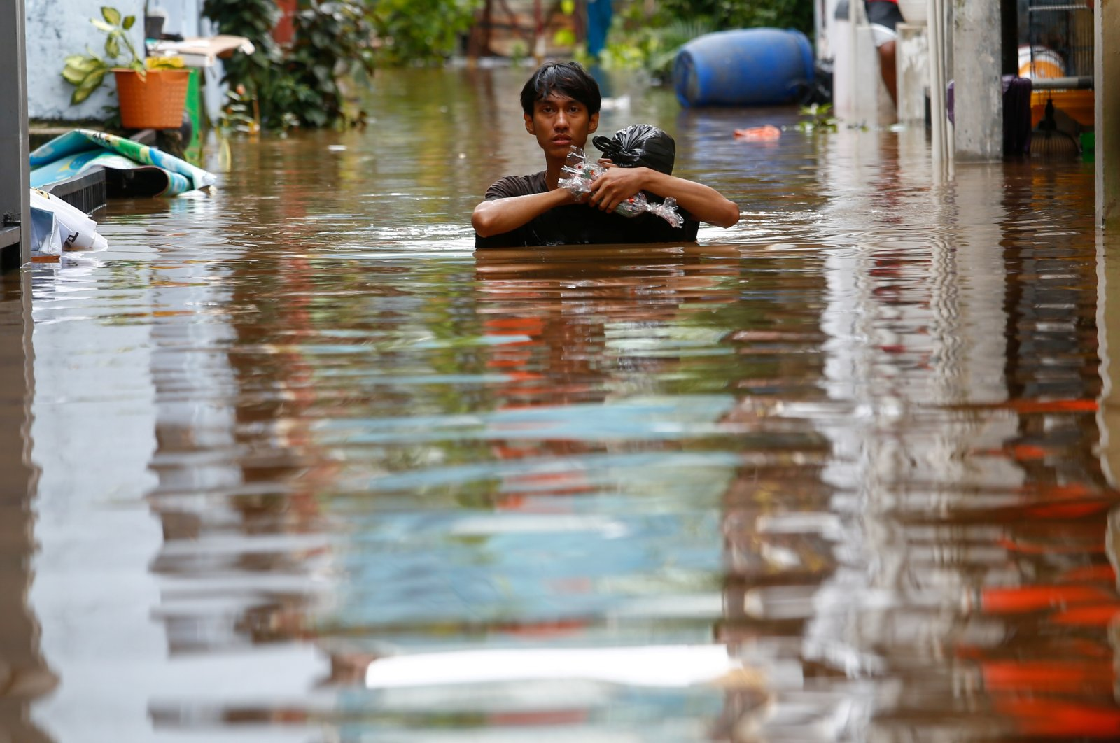 A man carrying his goods walks through the water in an area affected by floods, following heavy rains in Jakarta, Indonesia, Feb. 20, 2021. (Reuters Photo)
